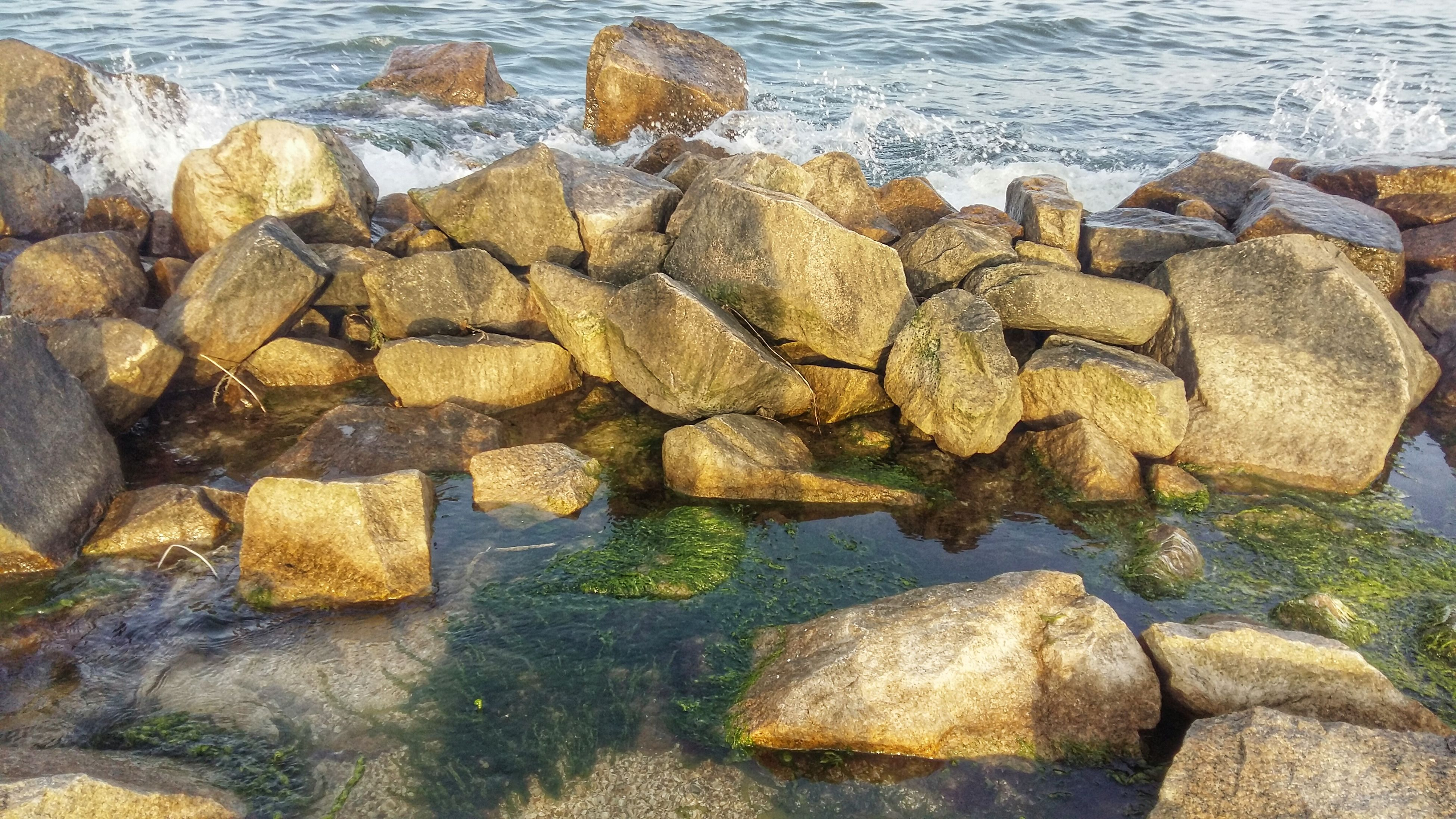 water, rock - object, sea, stone - object, rock, stone, stack, tranquility, nature, pebble, high angle view, shore, large group of objects, beach, rock formation, day, outdoors, tranquil scene, abundance, no people