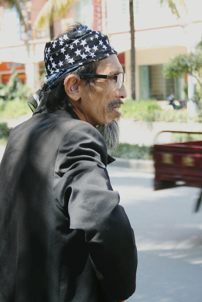 Side View Of Senior Man Wearing Headband Standing On Street