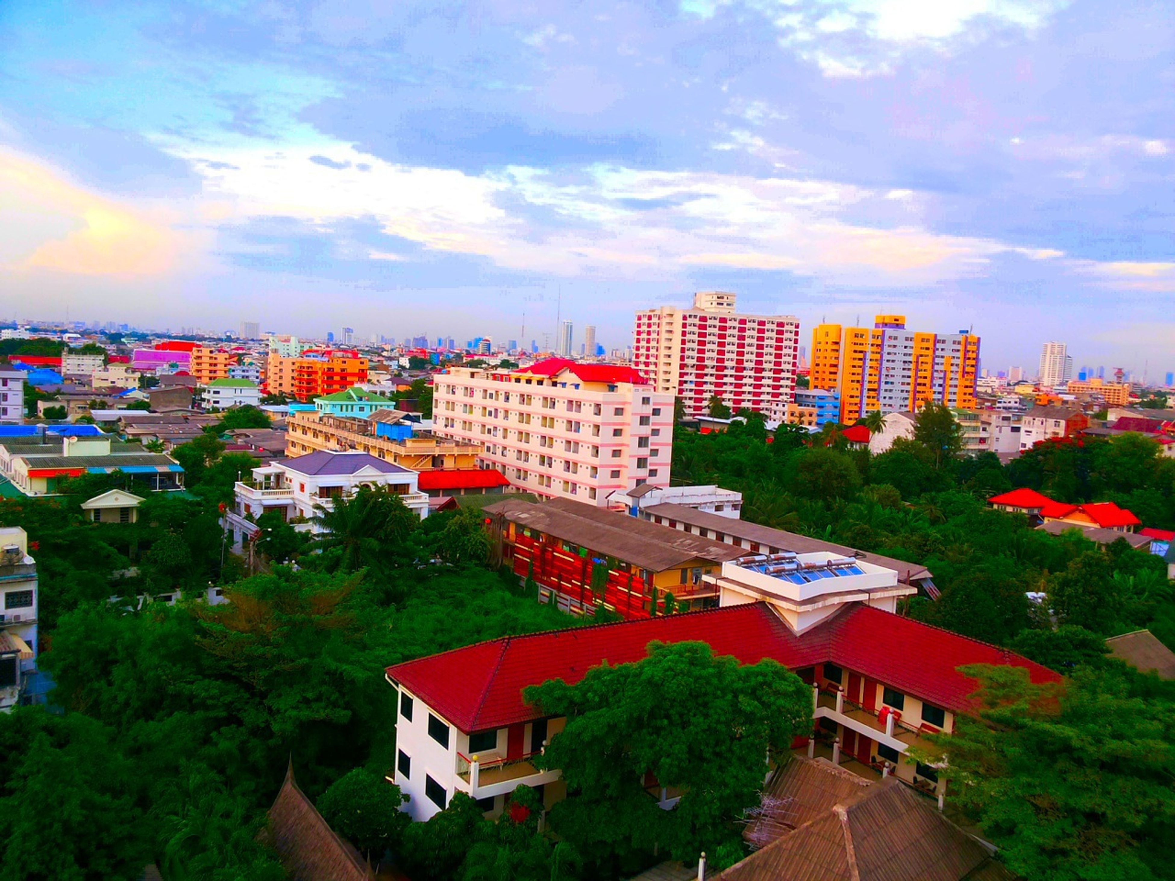 building exterior, architecture, built structure, sky, house, residential building, residential structure, residential district, high angle view, tree, city, roof, cloud - sky, cityscape, town, crowded, townscape, cloud, cloudy, outdoors