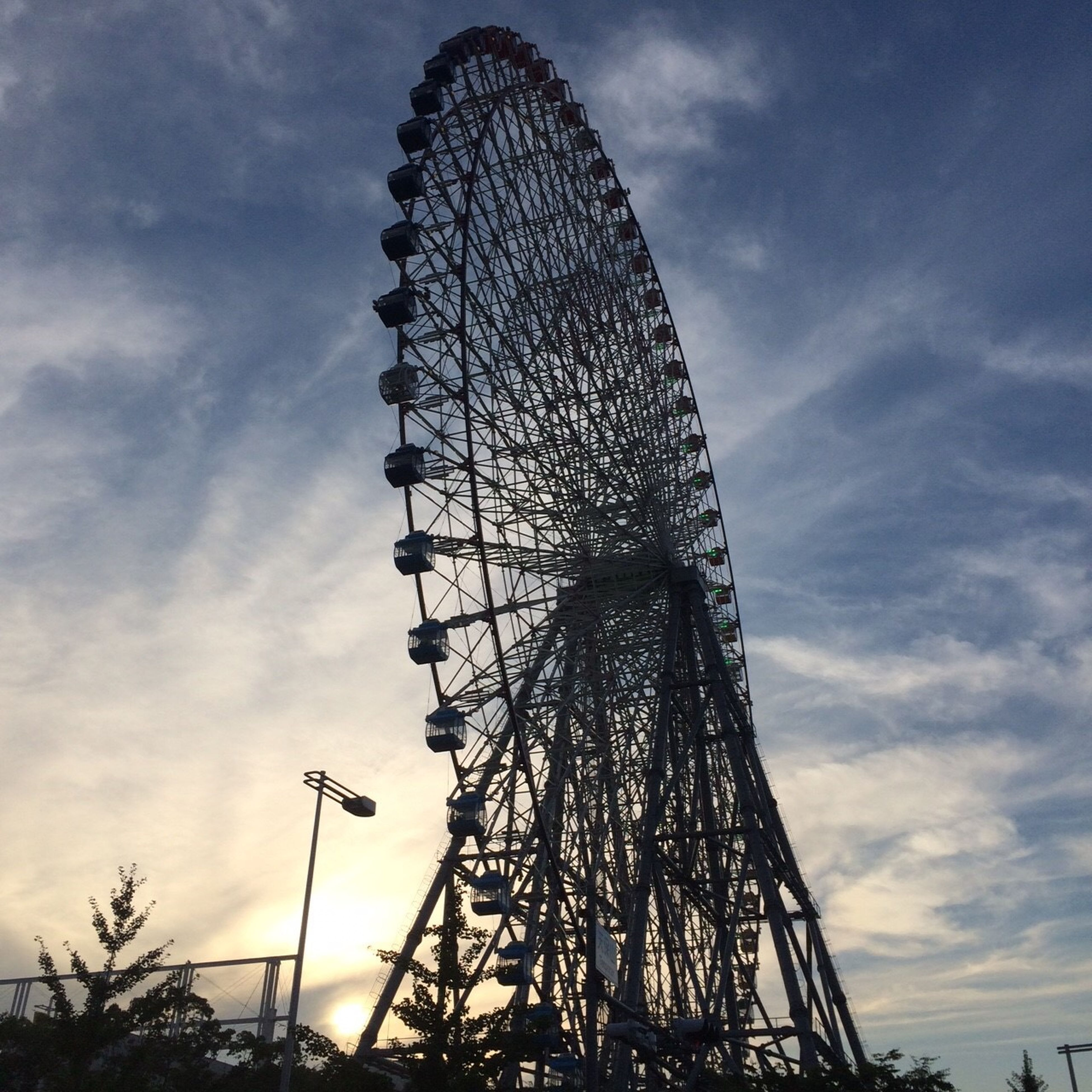 low angle view, sky, cloud - sky, silhouette, street light, cloudy, cloud, built structure, lighting equipment, tall - high, dusk, illuminated, architecture, outdoors, arts culture and entertainment, no people, ferris wheel, amusement park, amusement park ride, tree