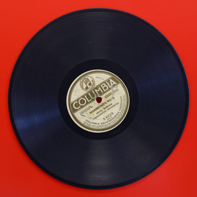 Early days of media market - old vintage vinyl music record over red Album Close-up Color Disc Industry Label Media Music Old Old-fashioned Record Red Release Retro Songs Technology The Color Of Technology Tracks Vibrant Vintage Vinyl Vinyl Records Vivid