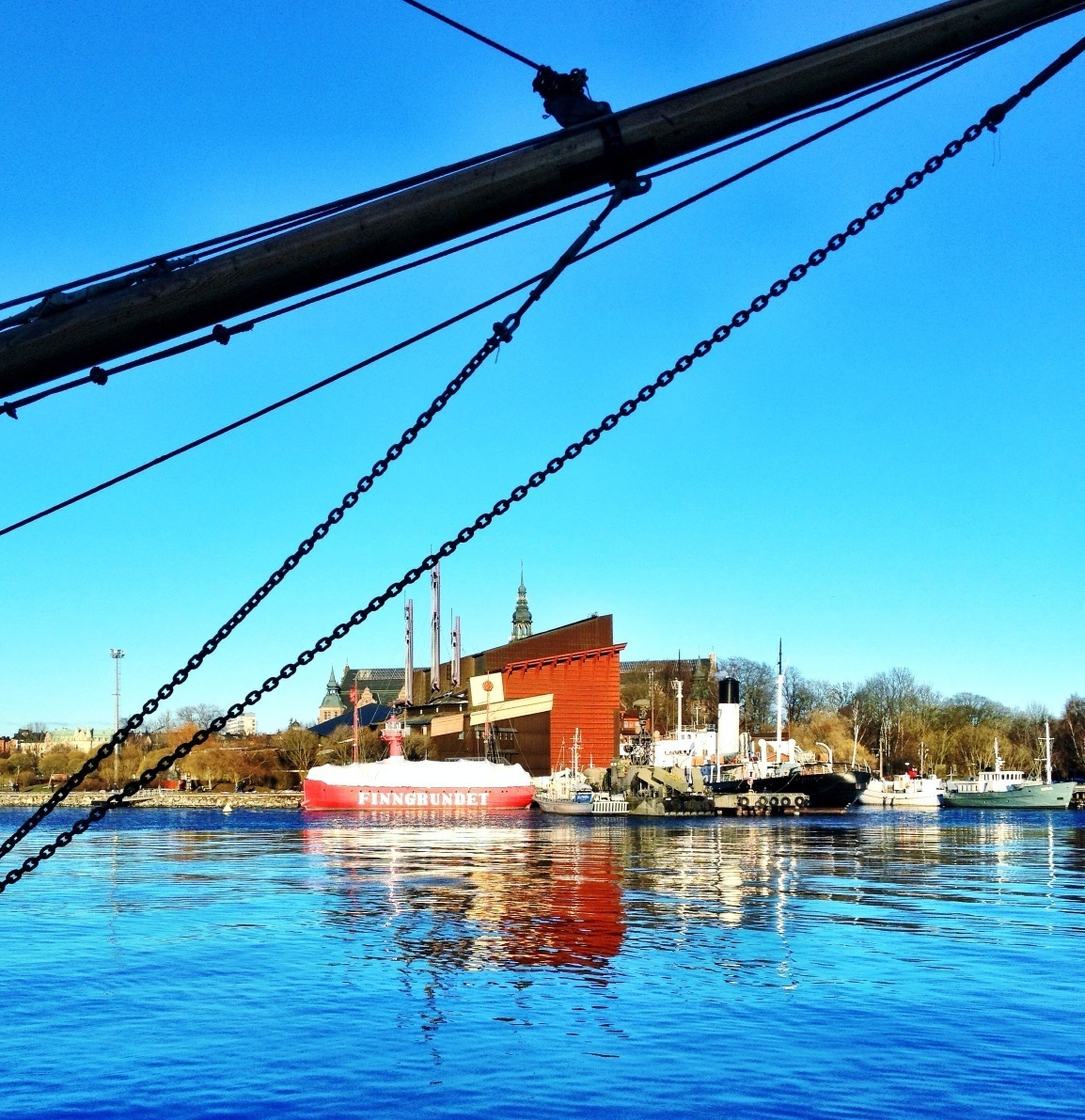 nautical vessel, transportation, blue, water, clear sky, boat, mode of transport, mast, waterfront, moored, built structure, sailboat, sky, river, day, harbor, architecture, reflection, travel, outdoors