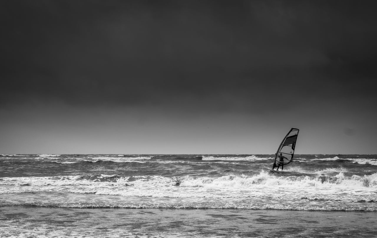 sea, water, horizon over water, nature, waterfront, windsurfing, wave, beauty in nature, extreme sports, sky, leisure activity, scenics, motion, sport, real people, day, surfing, outdoors, skill, one person, adventure, clear sky, men, people