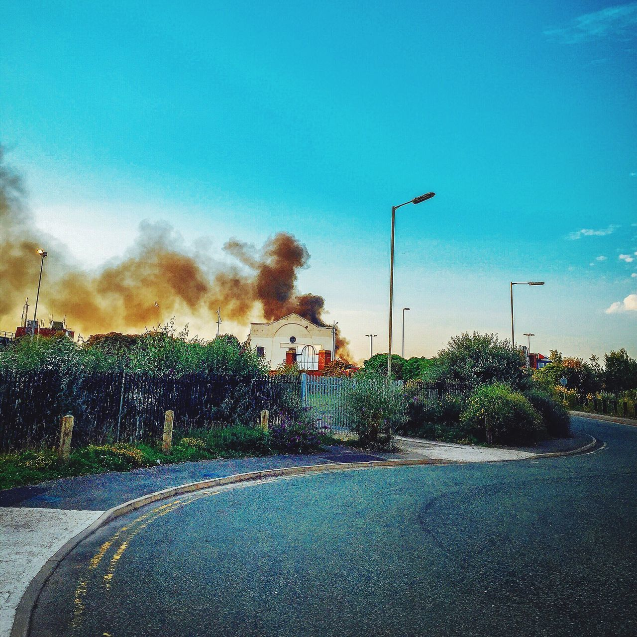 smoke - physical structure, built structure, tree, sky, no people, architecture, day, outdoors, road, building exterior, smoke stack, blue