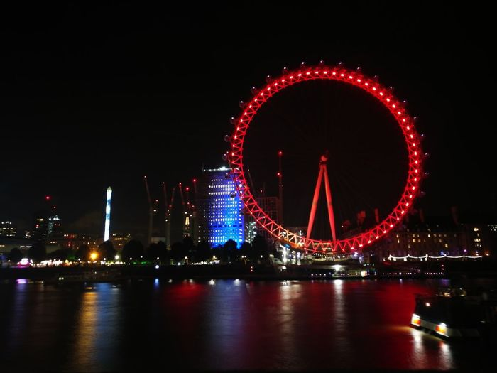 By night. London London Eye Night Illuminated Arts Culture And Entertainment City Long Exposure Travel Destinations Built Structure Red Cityscape Ferris Wheel Outdoors Celebration Multi Colored Event Firework Display No People Building Exterior Architecture Sky Nightlife Travel Riverside Reflection