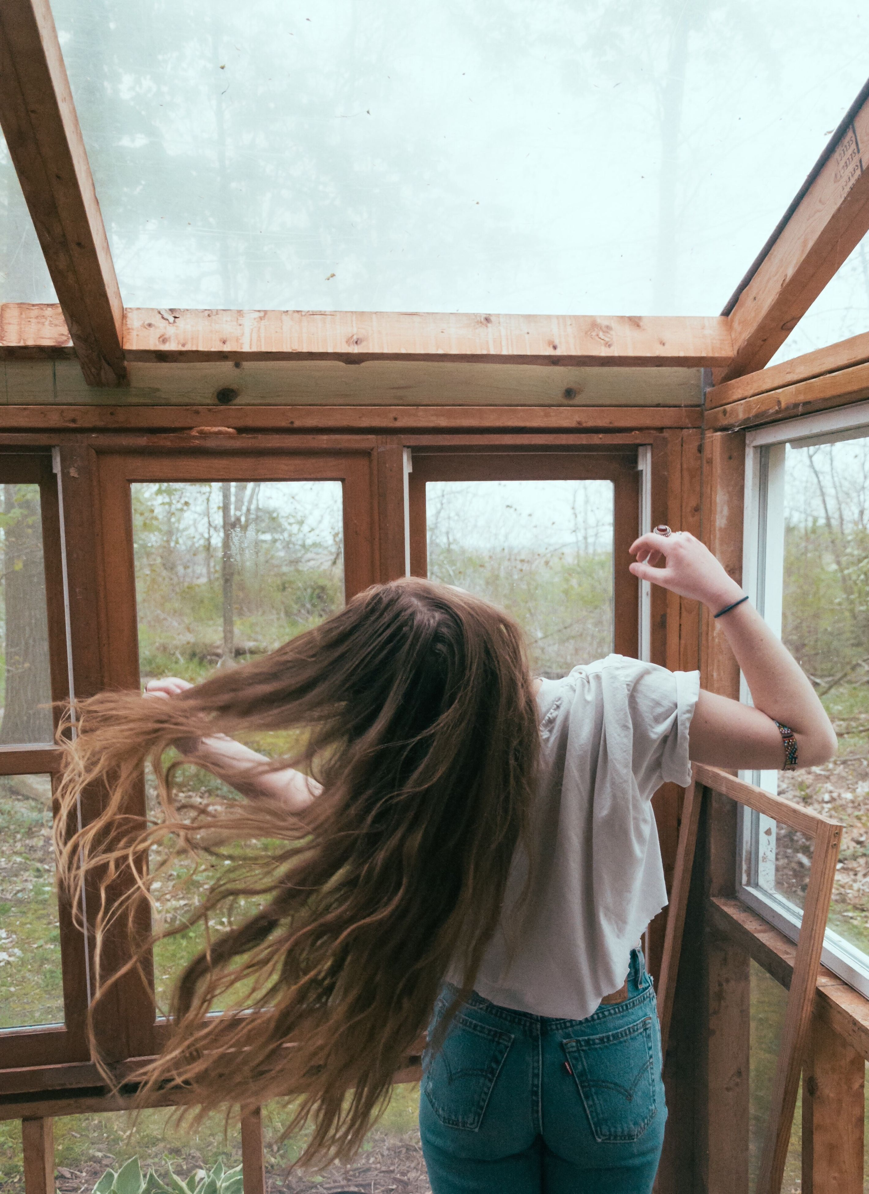 indoors, lifestyles, young adult, window, leisure activity, person, young women, casual clothing, long hair, home interior, relaxation, sitting, rear view, headshot, built structure, waist up, day, house