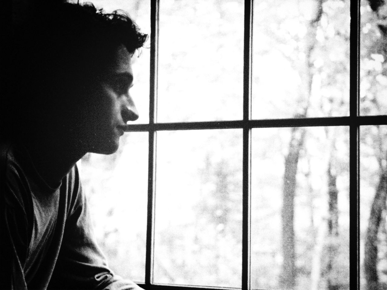window, indoors, one person, real people, side view, looking through window, home interior, lifestyles, day, close-up, young adult