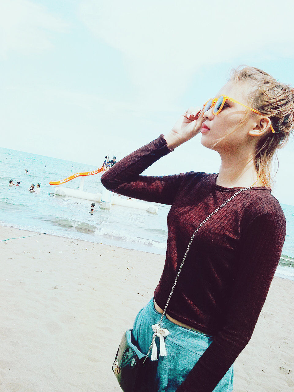 Young Woman Looking Away While Standing At Beach