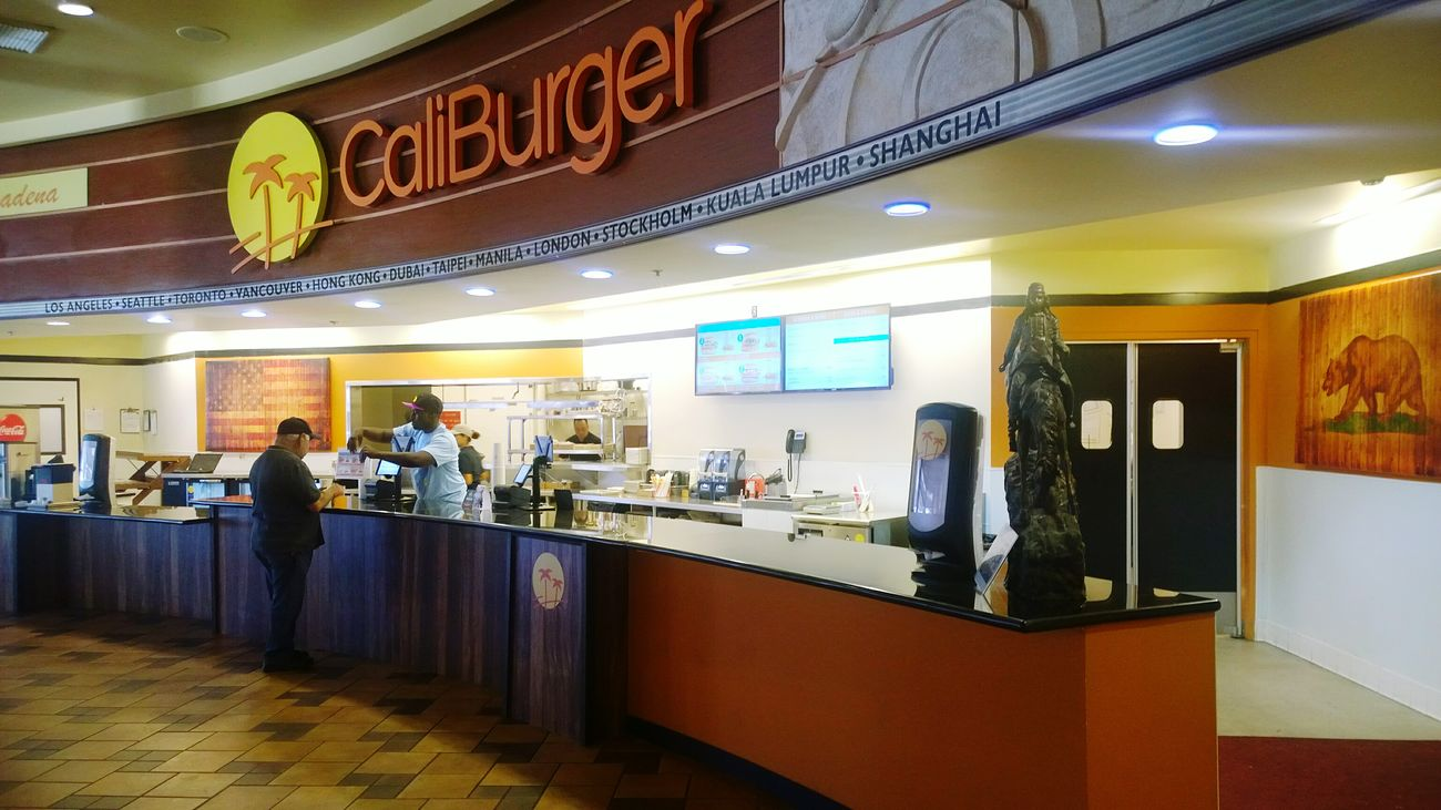 Caliburger Register Cashier  Customer  Pattern Floor Lights Menu Condiments  Working Sign Indoors  Restaurant Hamburger Architecture Eating Doors City Names