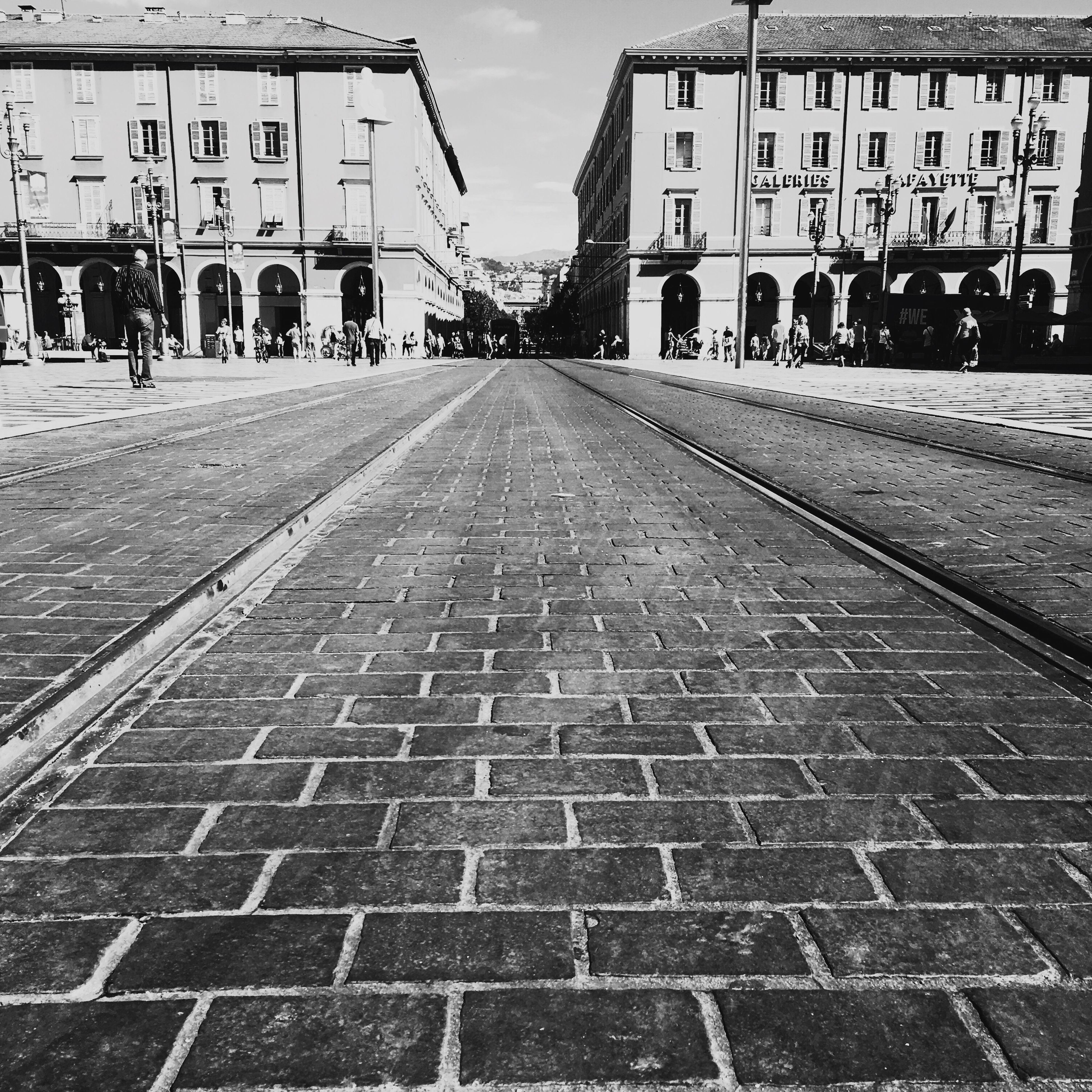 architecture, building exterior, built structure, the way forward, street, city, surface level, mid distance, day, outdoors, footpath, sky, city life, diminishing perspective, long, paving stone, geometric shape, pedestrian walkway