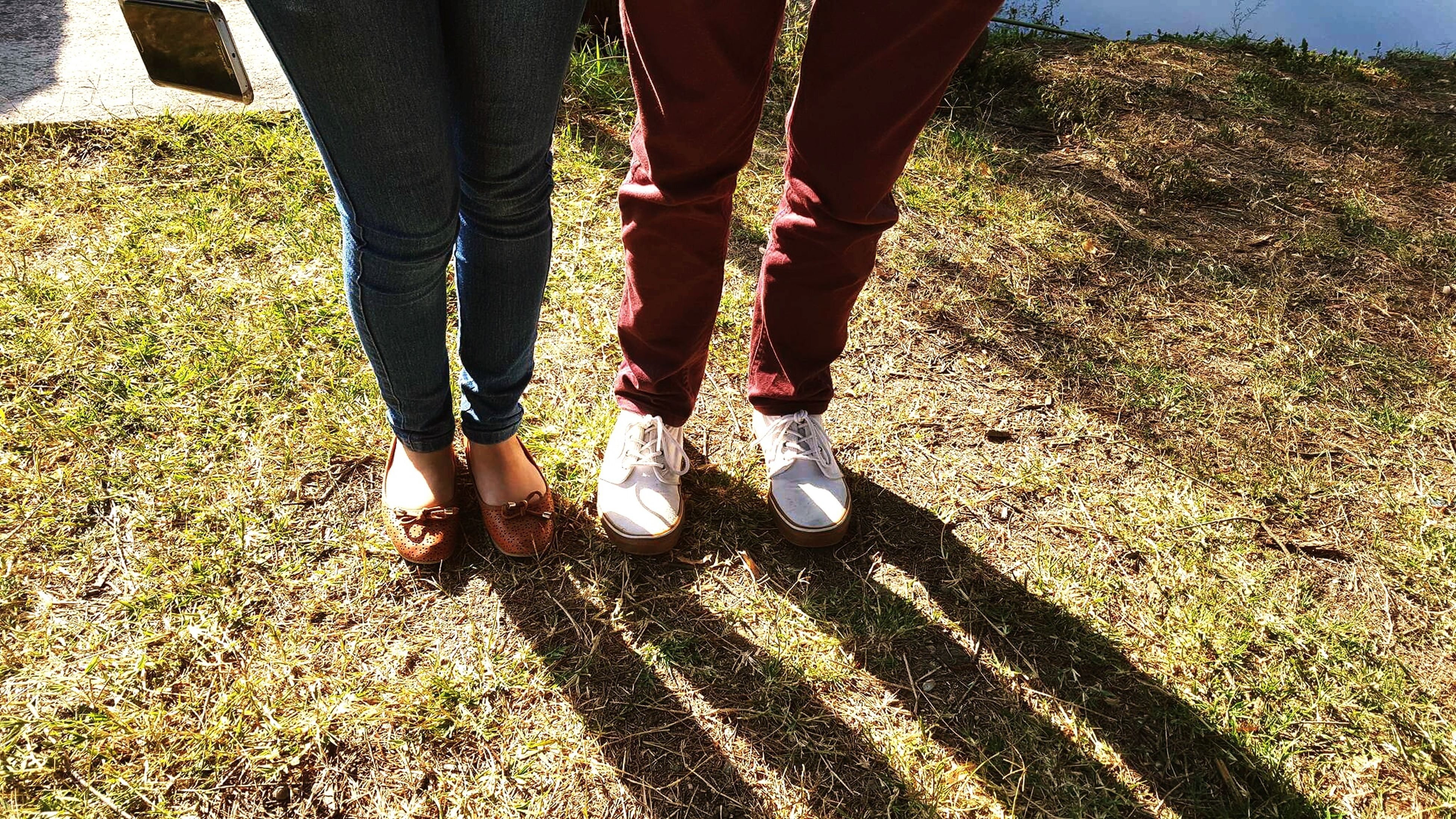 low section, person, lifestyles, standing, leisure activity, shoe, human foot, togetherness, men, bonding, casual clothing, field, grass, jeans, friendship
