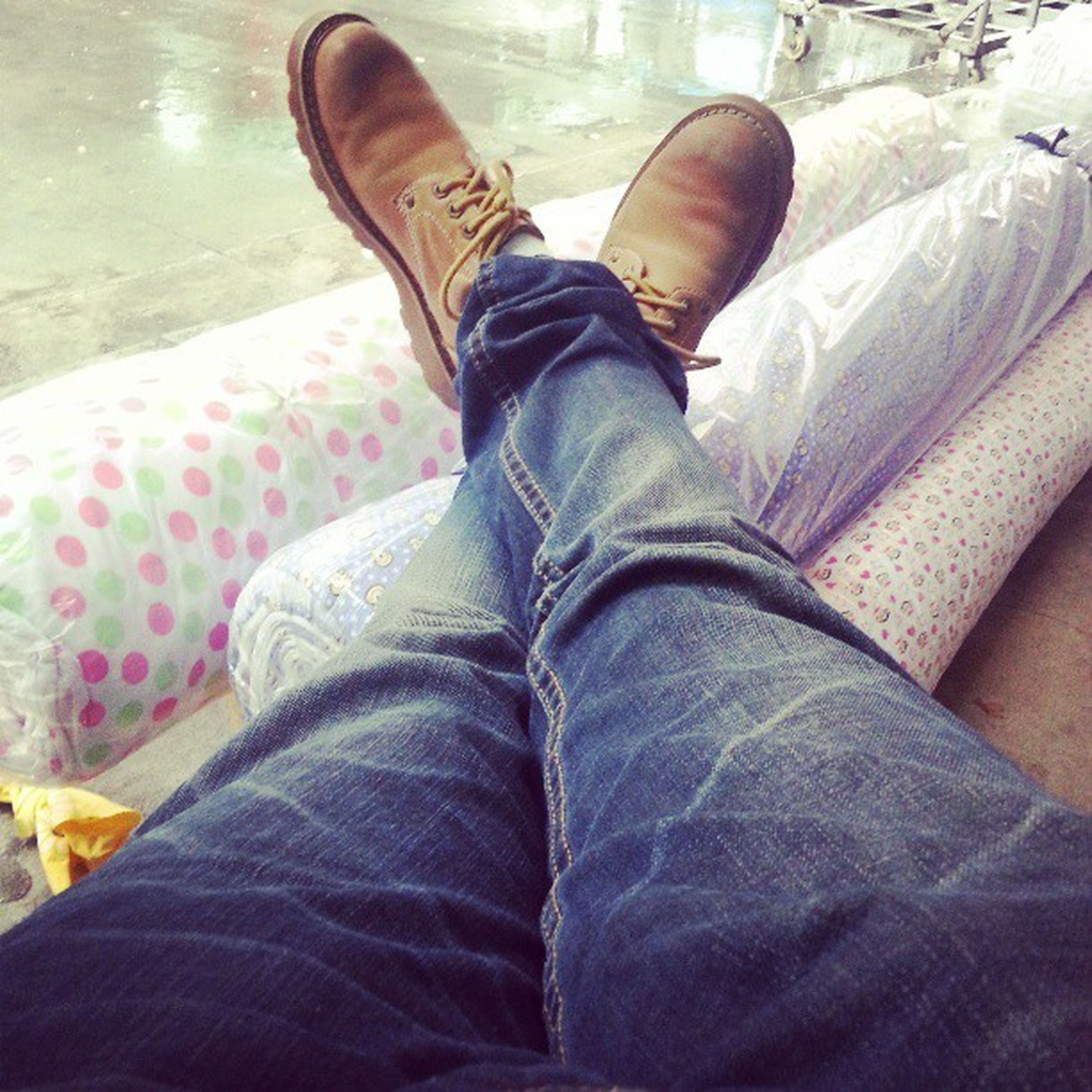 low section, person, shoe, jeans, personal perspective, indoors, lifestyles, human foot, relaxation, men, footwear, casual clothing, sitting, leisure activity, standing, high angle view, directly above
