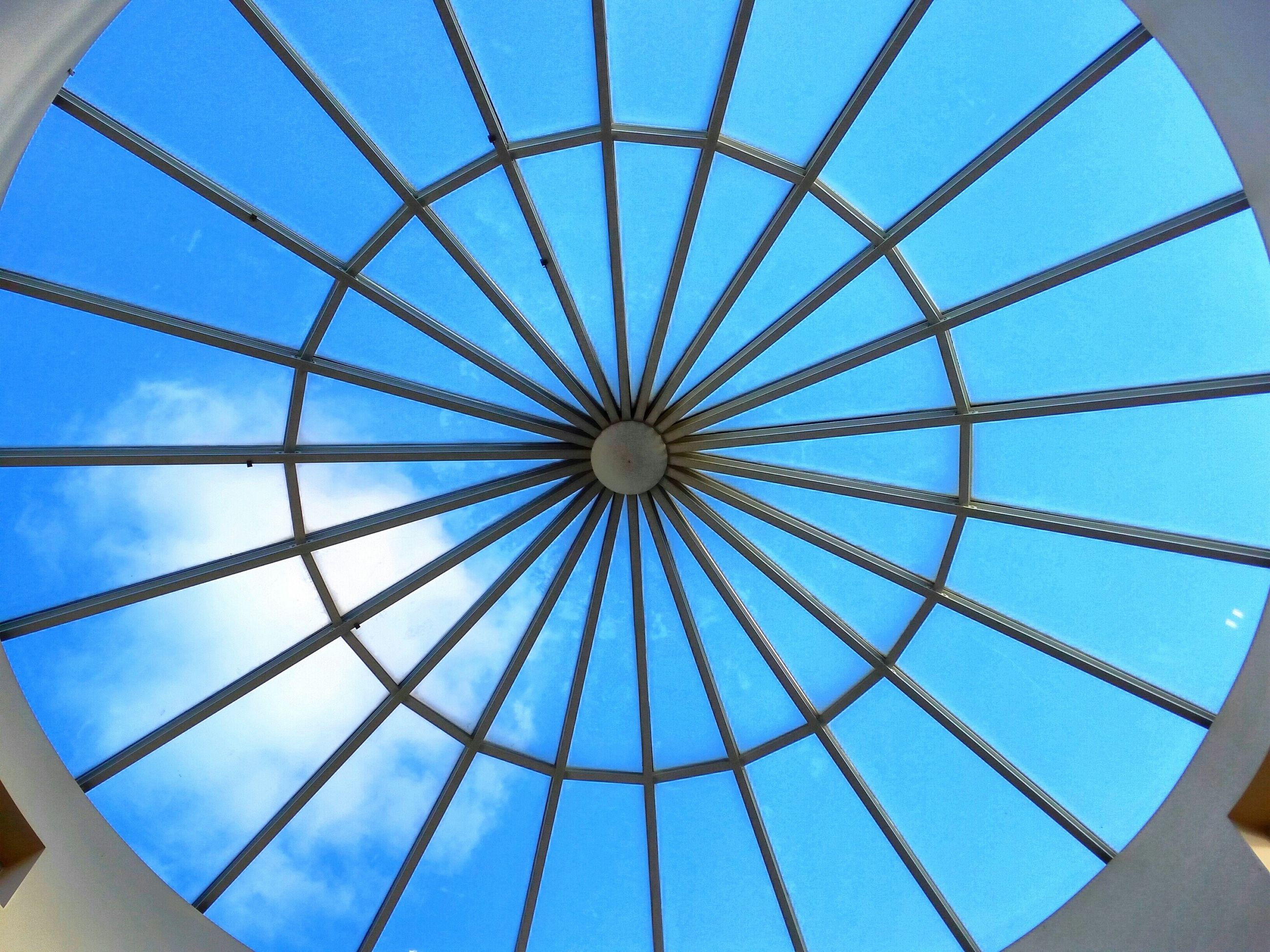 low angle view, blue, pattern, sky, geometric shape, directly below, built structure, design, architecture, ceiling, metal, full frame, circle, backgrounds, indoors, skylight, day, metallic, cloud - sky, no people