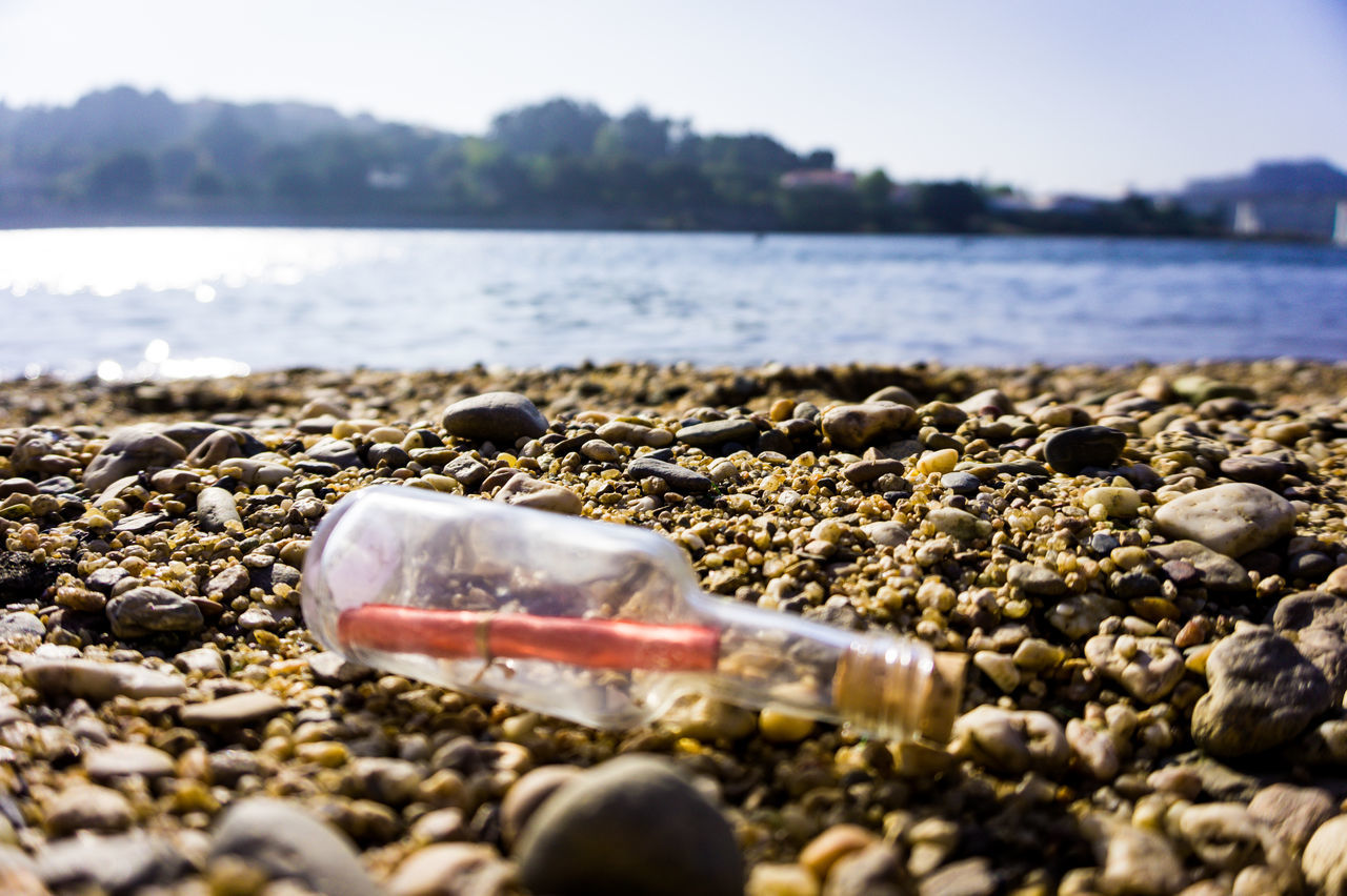 Beach Calm Coastline Day Message In A Bottle Nature Outdoors Pebble Pebble Beach Riverbank Sand Scenics Sea Secret Selective Focus Shore Stone - Object Summer Surface Level Tranquil Scene Tranquility Vacations Water