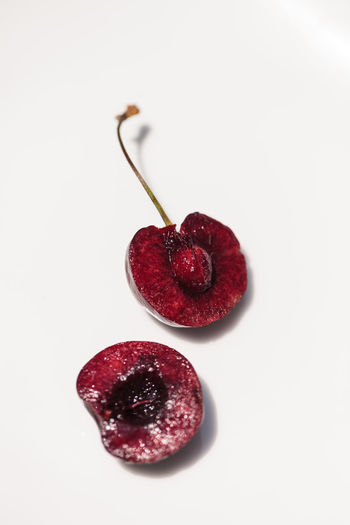Macro of a dark red black cherry with a green stem on a white background. Cherry Close-up Dark Red  Freshness Fruit Healthy Eating Juicy Juicy Fruit Macro No People Pit Sliced Fruit Stem Studio Shot White Background