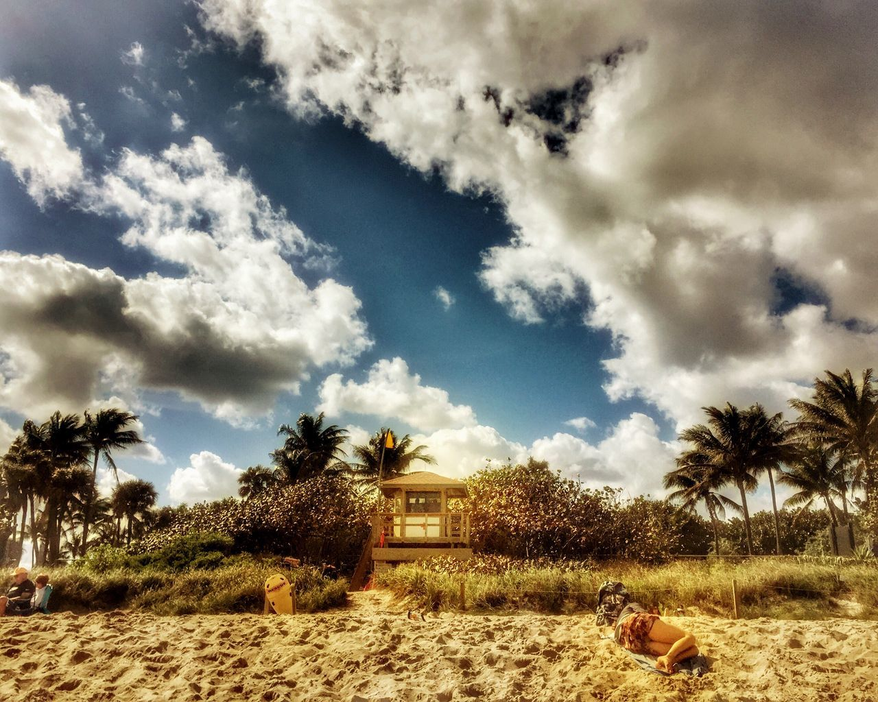 People Resting At Beach Against Cloudy Sky