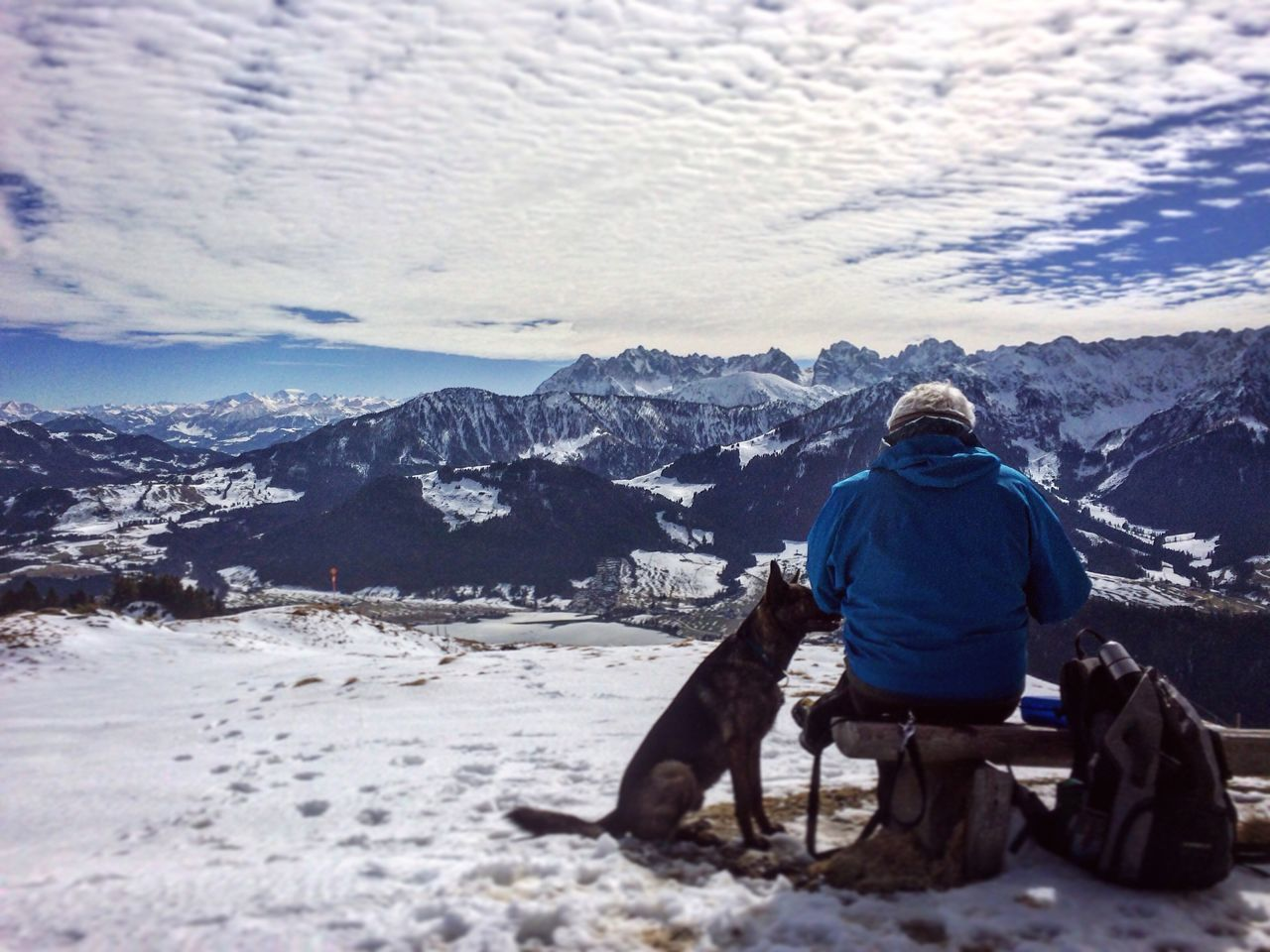 Man sitting on the top of the mountain and enjoys the stunning view with his dog Winter Snow Cold Temperature Sitting One Person Warm Clothing Nature Mountain Leisure Activity Full Length Rear View Outdoors Beauty In Nature Real People Day Sky Dog View Gipfel People Adult