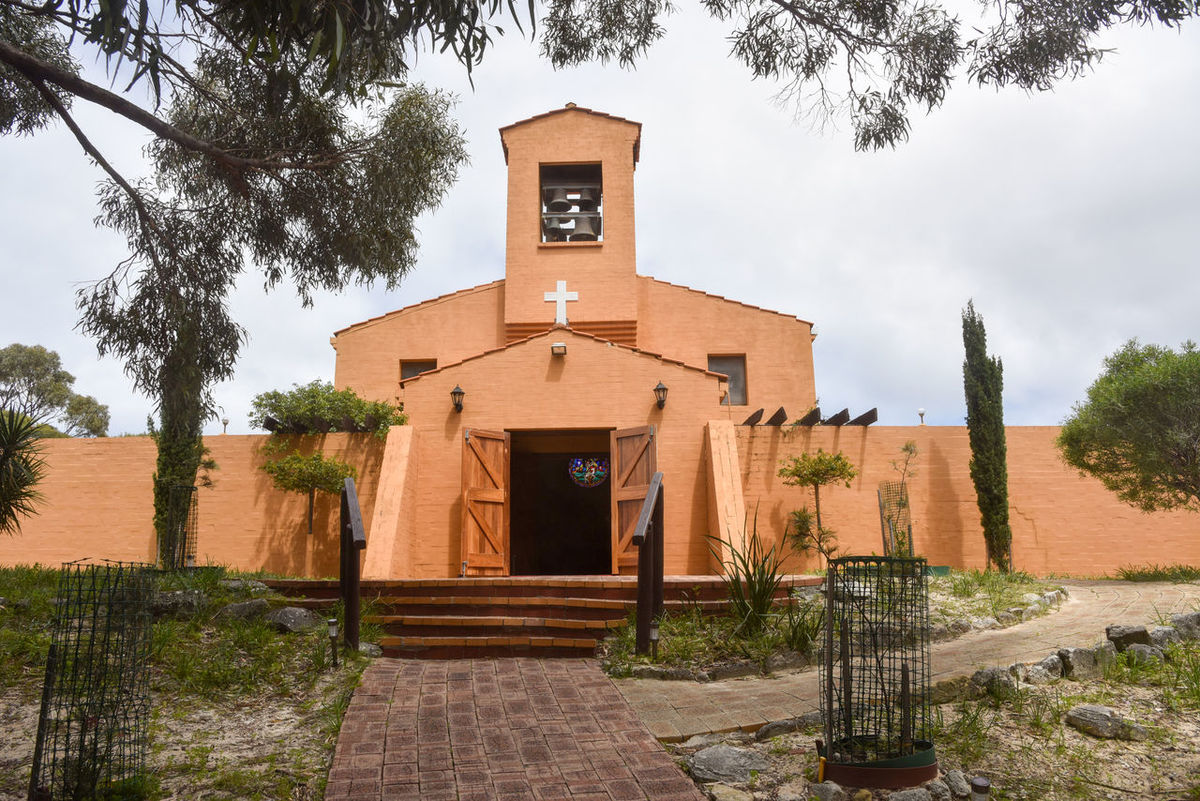 Front view of the Spanish architecture of the Catholic Church of the Holy Trinity on Rottnest Island in Western Australia. Architecture Bell Building Catholic Chapel Church Church Bell Cross Doorway Entrance Exterior Façade Hilltop Holy Trinity Island Place Of Worship Religious  Rottnest Spanish Spiritual Stucco Thompson Bay Tourist Attraction  Travel Destinations Western Australia
