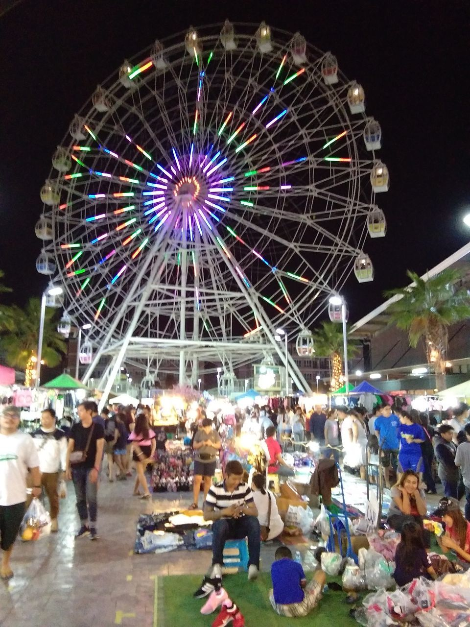 amusement park, ferris wheel, arts culture and entertainment, amusement park ride, large group of people, leisure activity, illuminated, night, enjoyment, low angle view, sky, outdoors, group of people, carousel, people