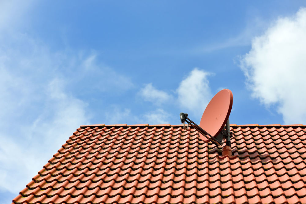 A satellite dish on a house roof Antenna Blue Cloud Cloud - Sky Cloudy Day Dvb DVBS High Section Low Angle View No People Outdoors Radio Red Roof Roof Rooftop Satellite Antennas Satellite Dishes Sky Sunny Day Sunny☀ Tv