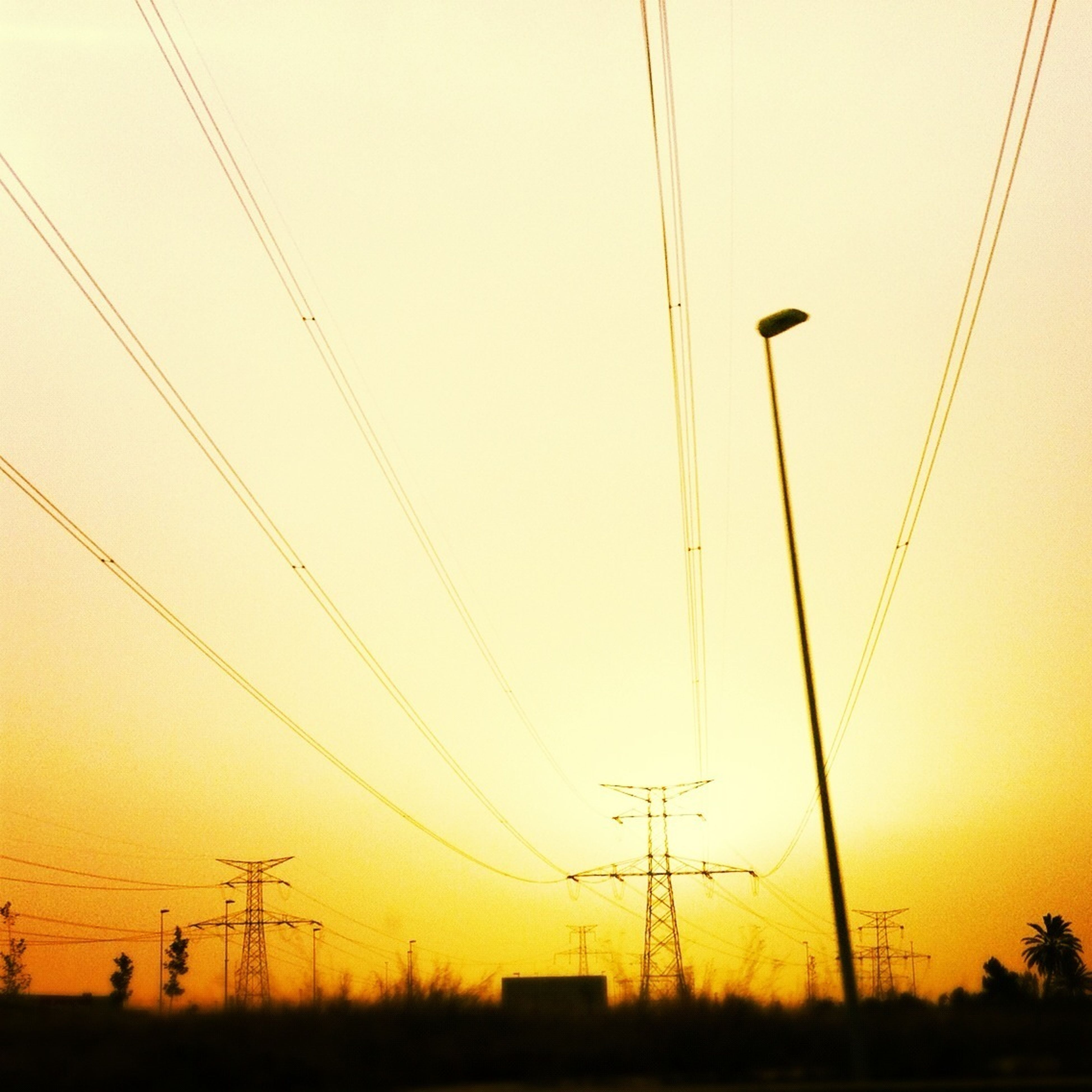 power line, electricity pylon, power supply, electricity, sunset, connection, cable, fuel and power generation, silhouette, technology, low angle view, power cable, sky, orange color, no people, nature, outdoors, telephone pole, scenics, tranquility