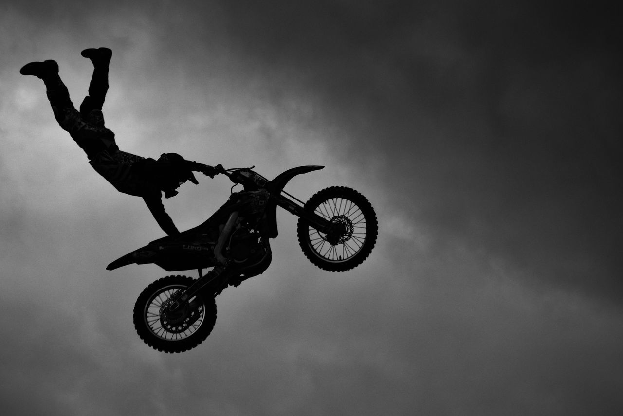 Low Angle View Of Biker Performing Stunt In Mid-Air Against Cloudy Sky