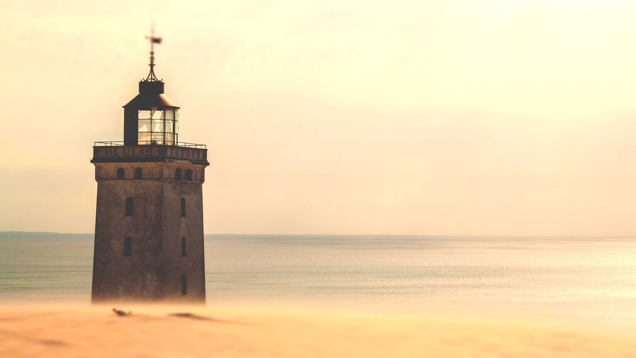 sea, lighthouse, architecture, horizon over water, guidance, sunset, tower, direction, beach, water, built structure, sky, building exterior, protection, tranquil scene, tranquility, beauty in nature, sand, nature, no people, outdoors, scenics, day