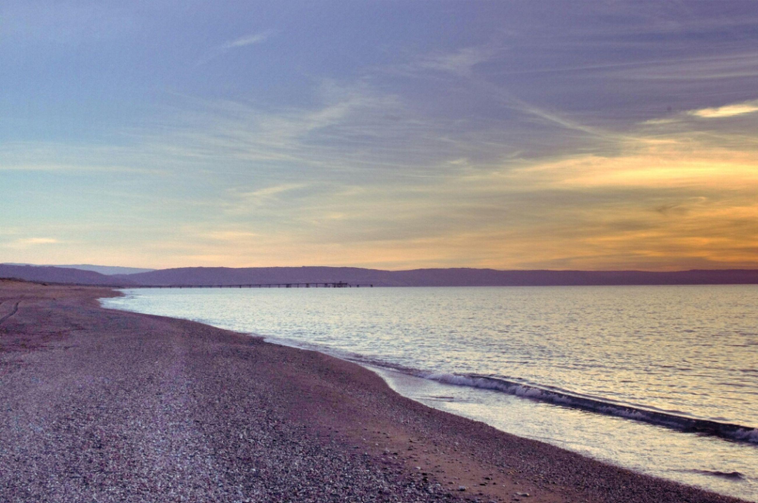 sea, beach, water, tranquil scene, scenics, tranquility, beauty in nature, sunset, sky, shore, sand, horizon over water, nature, idyllic, cloud - sky, coastline, cloud, non-urban scene, remote, outdoors
