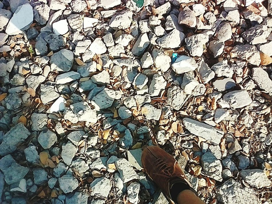 Just strolling. Rocks Outdoors Human Leg Sunlight Shadow And Light Brown Gray