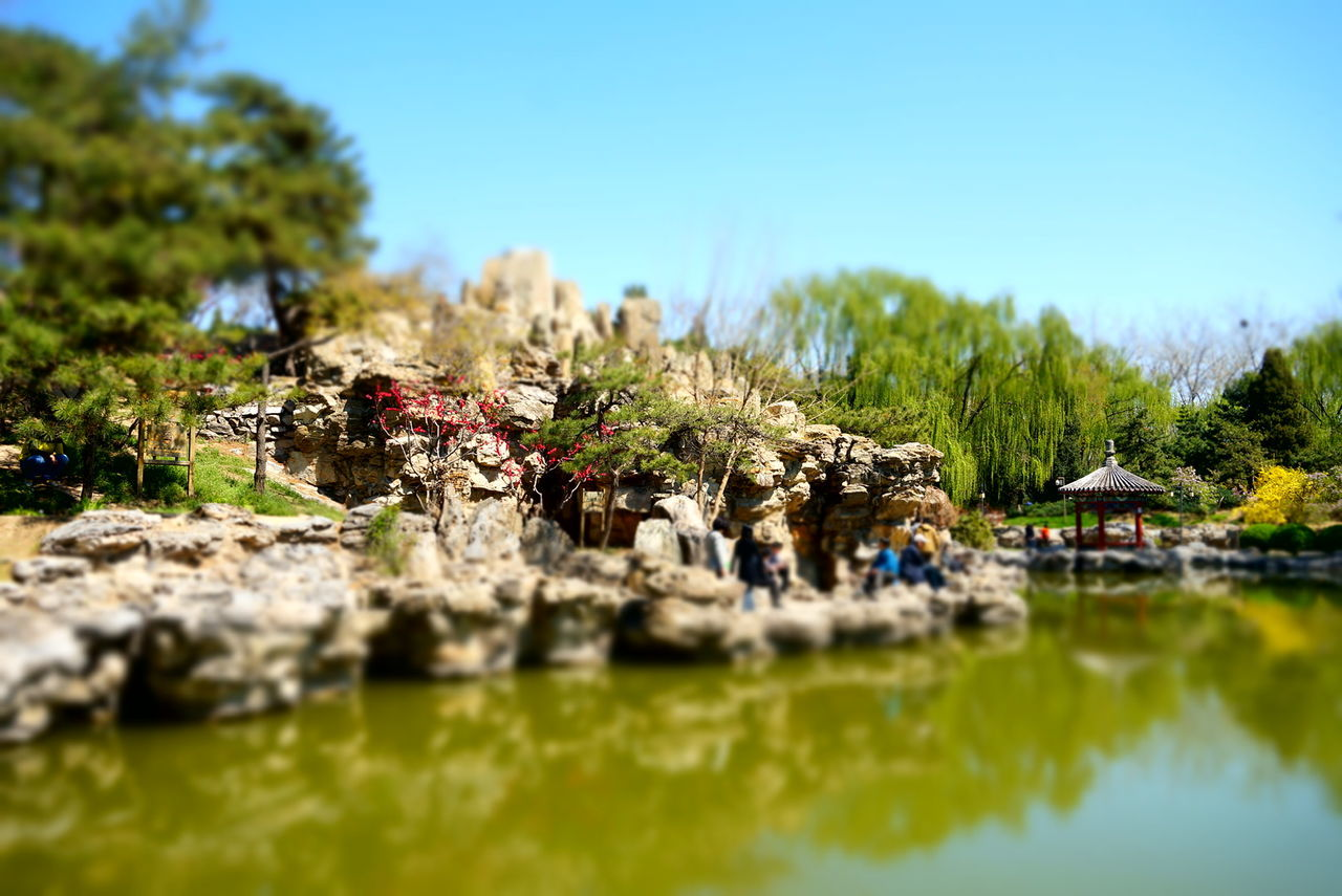 Rocks And Pond At Ritan Park Against Clear Blue Sky