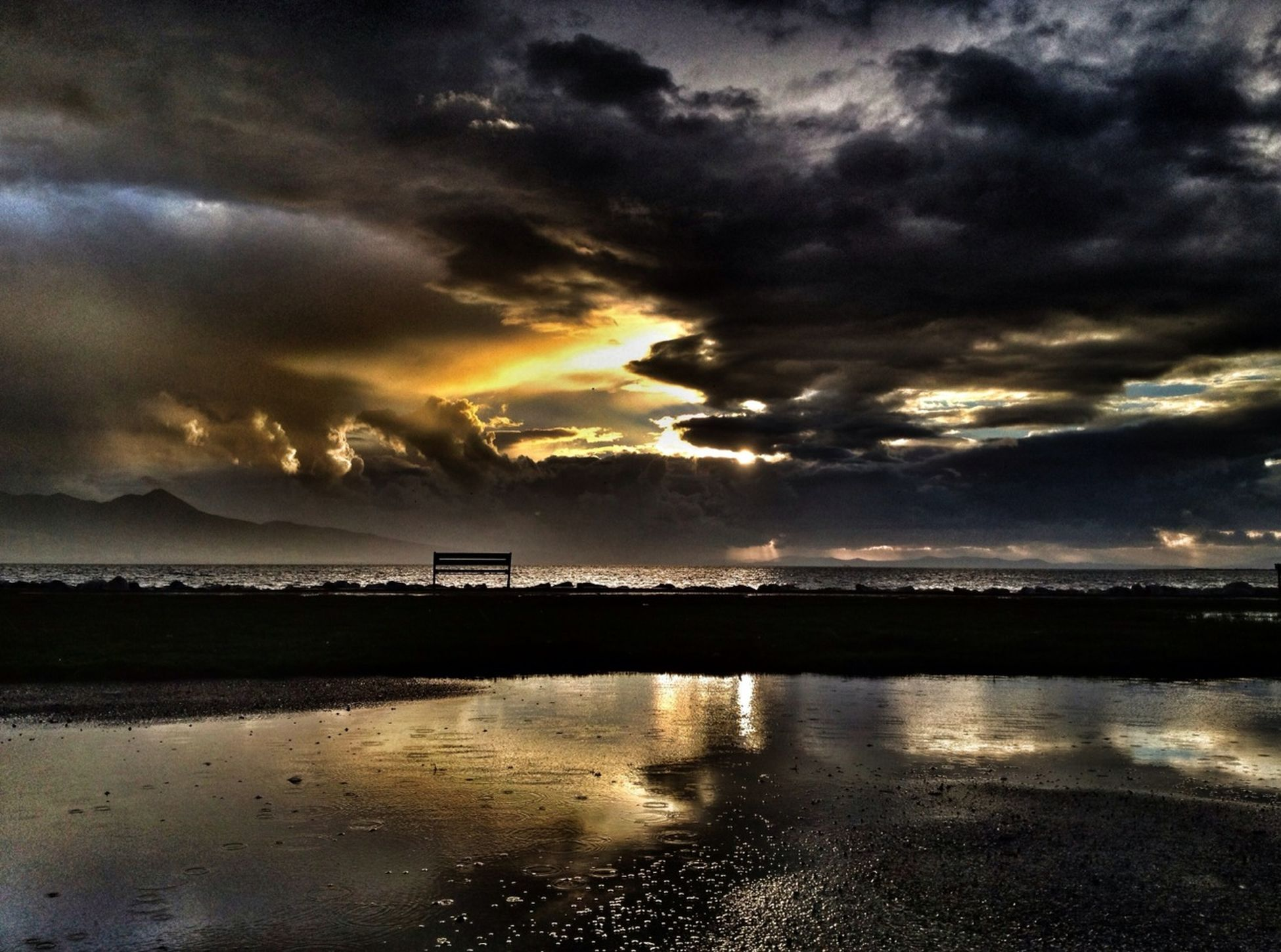 water, sunset, sky, cloud - sky, scenics, tranquil scene, tranquility, cloudy, reflection, beauty in nature, sea, dramatic sky, weather, nature, idyllic, cloud, atmospheric mood, overcast, beach, waterfront