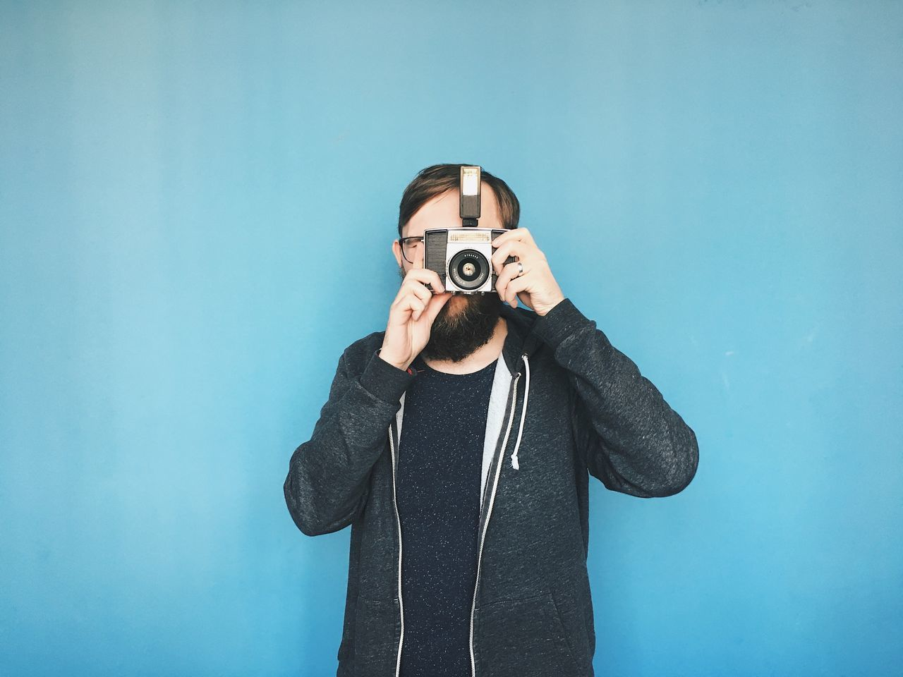 Analog Camera - Photographic Equipment Casual Clothing Colored Background Front View Holding Old-fashioned One Man Only One Person Photographing Photography Themes Portrait Real People Technology Waist Up Young Adult