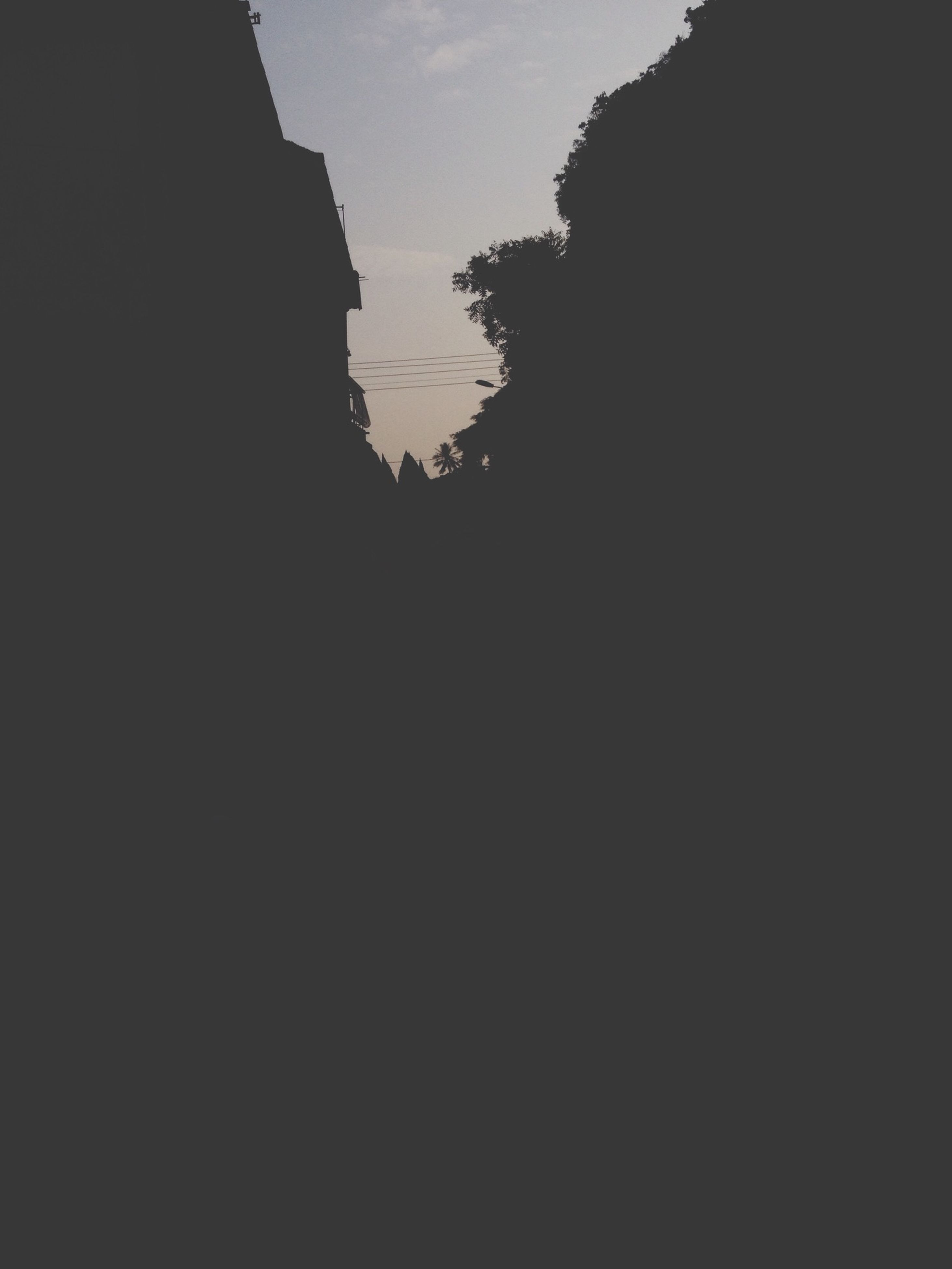 silhouette, sky, tranquility, tranquil scene, beauty in nature, scenics, nature, low angle view, dark, tree, dusk, copy space, outdoors, mountain, no people, idyllic, clear sky, sunset, rock formation, outline