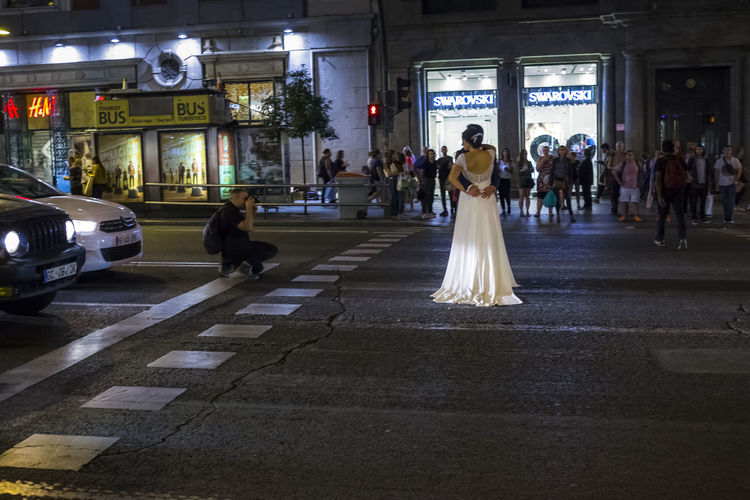 Bride and Groom in Gran Via Madrid during a photo shoot. City Life City Street Couple Groom Love Taking Photos Wedding Architecture Bride Bridegroom City Illuminated Large Group Of People Men Night People Posing Real People Text Transportation Travel Walking Wedding Day Wedding Dress Women