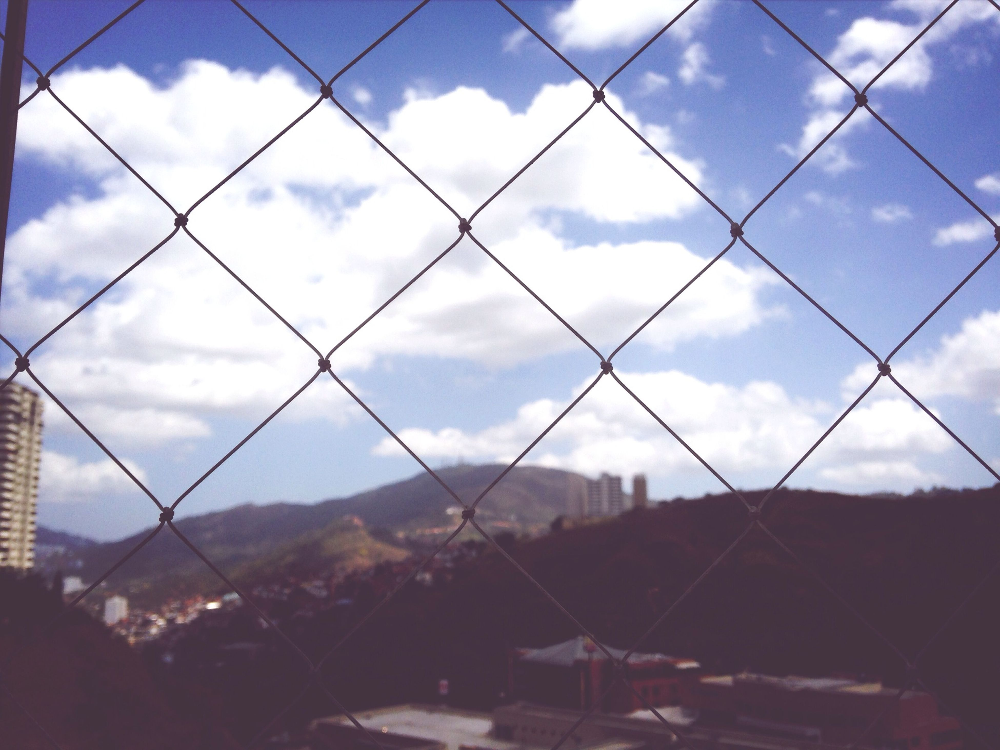 sky, cloud - sky, cloudy, cloud, built structure, architecture, building exterior, chainlink fence, fence, city, day, no people, landscape, cityscape, metal, outdoors, overcast, nature, weather, protection