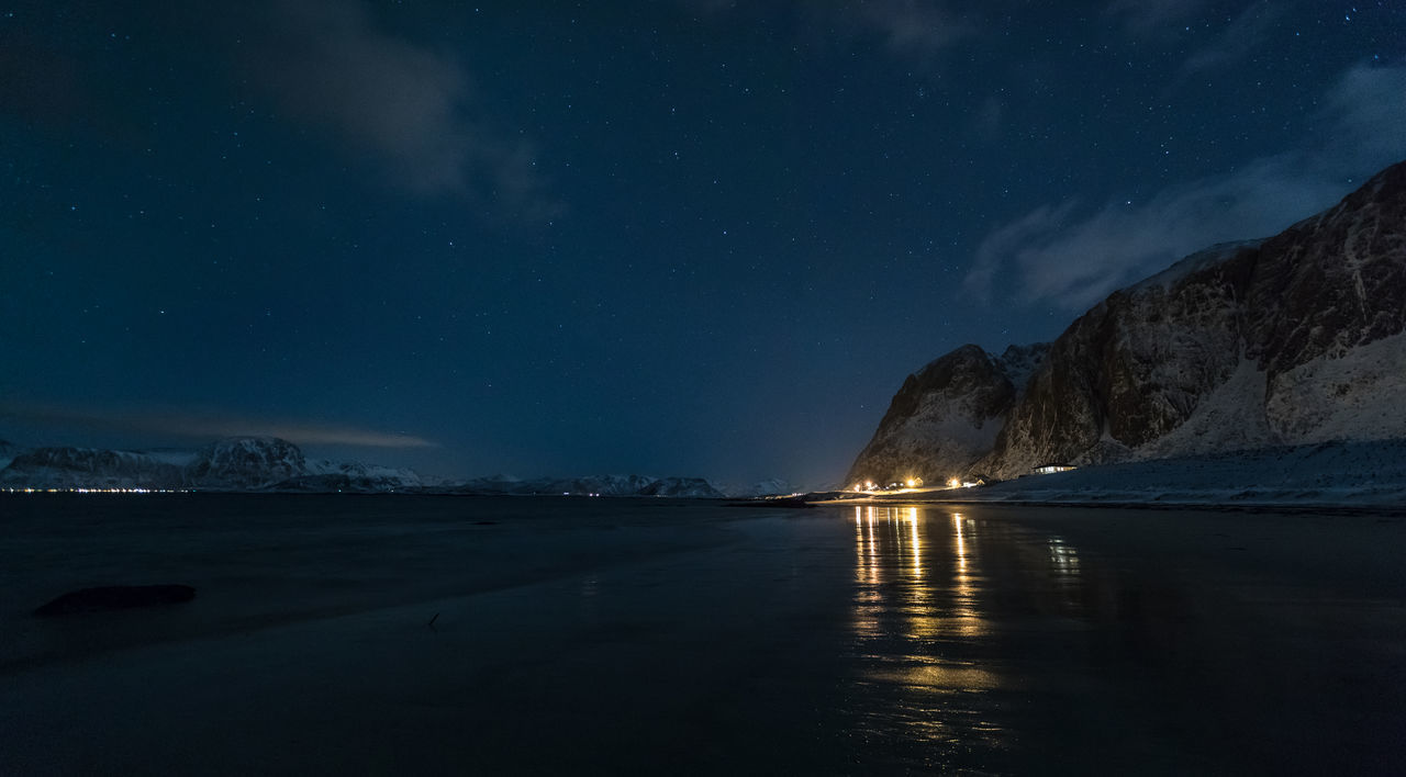 Panoramic view of mountain range and reflections on beach at night Astronomy Beach Beauty In Nature Coastline Cold Temperature Fjord Frozen Illuminated Landscape Lofoten And Vesteral Islands Mountain Mountain Range Nature Night Panoramic Reflection Remote Sea Sky Snow Space And Astronomy Star - Space Village Wet Winter