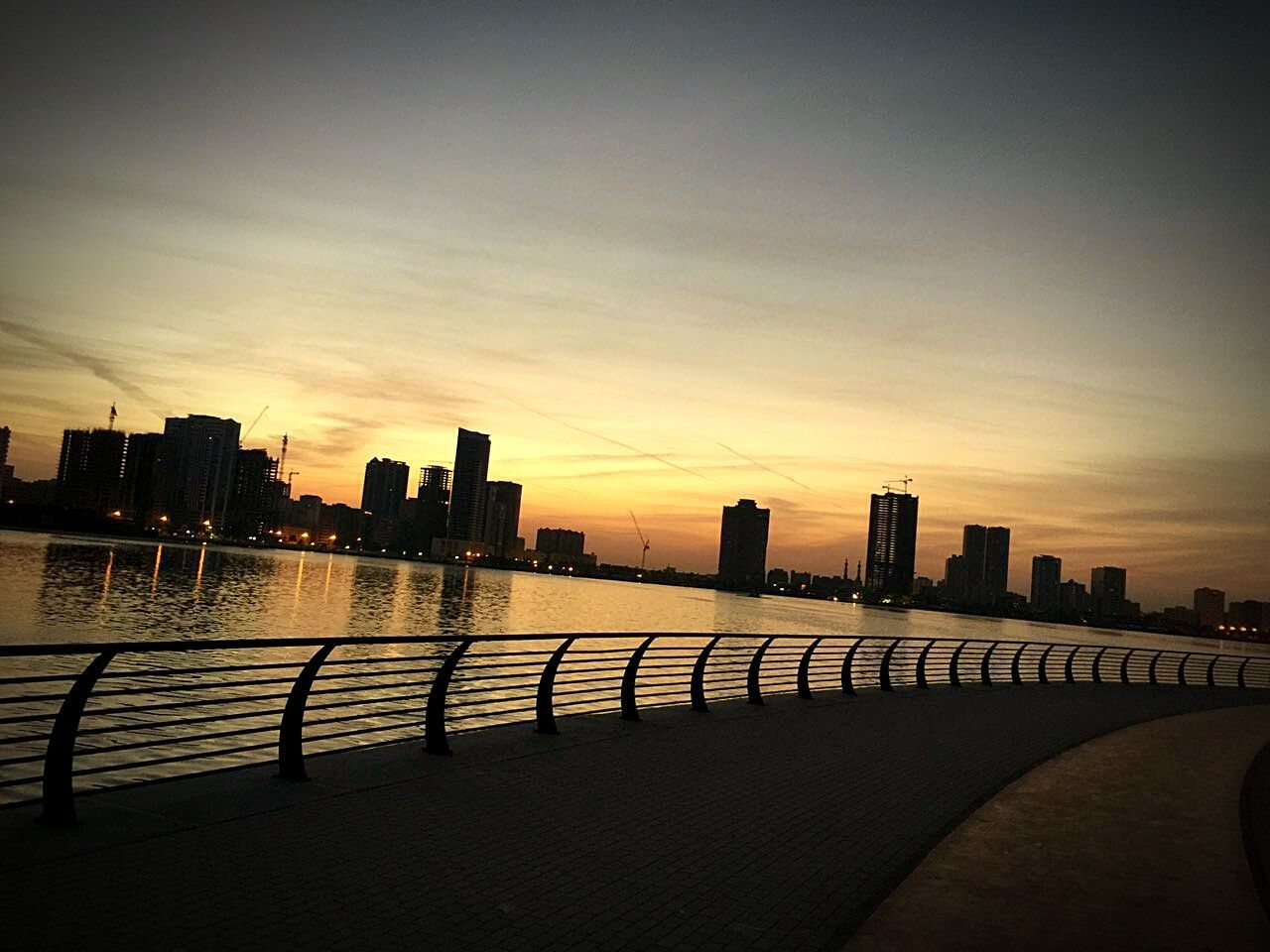 sunset, architecture, building exterior, built structure, skyscraper, city, railing, sky, no people, outdoors, travel destinations, modern, water, urban skyline, cityscape, day