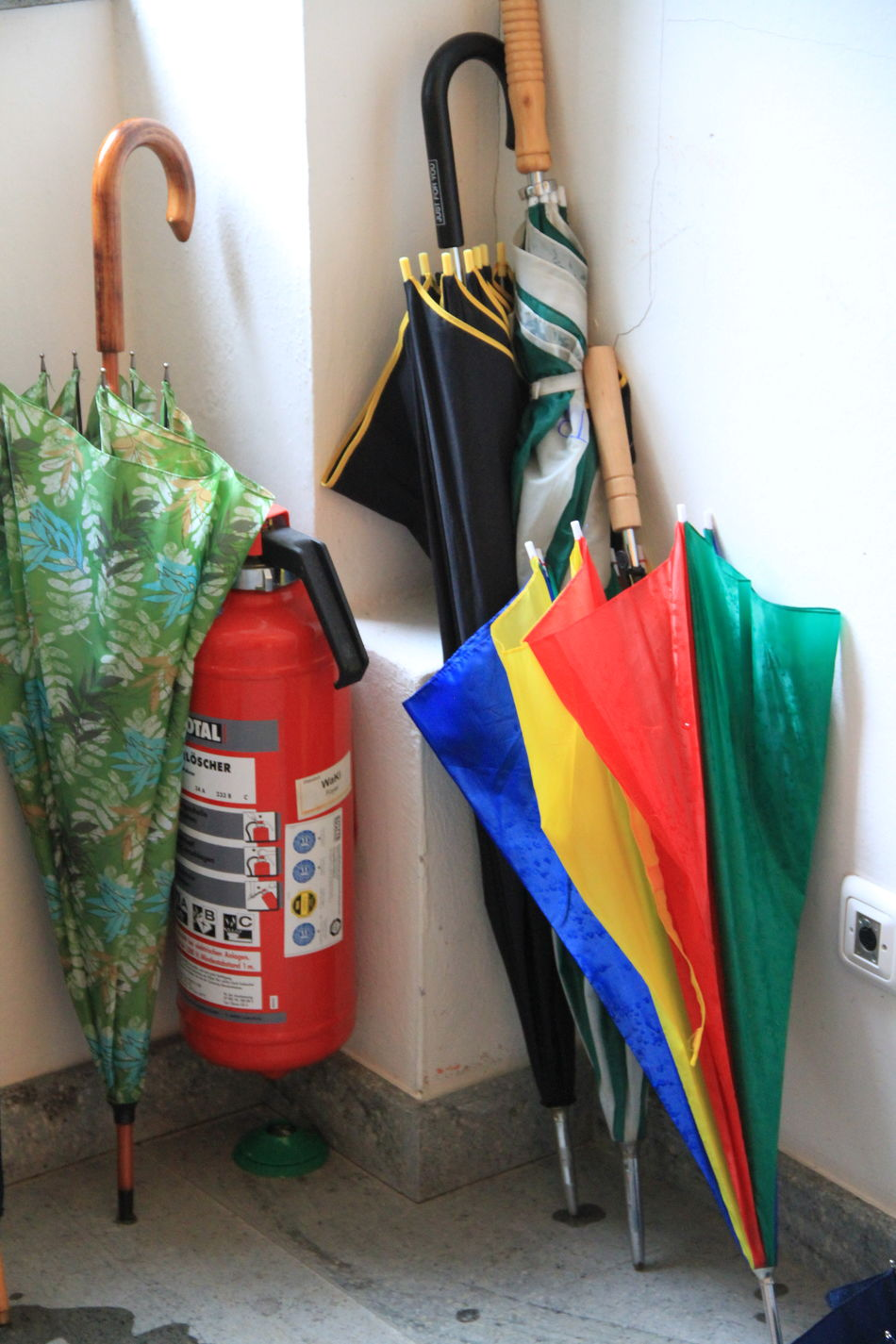 Be Prepared Brothers In Arms  Colorful Contrast Corner Fire Extinguisher Group Of Objects Multi Colored Never Know Preparation  Side By Side Umbrellas Wet And Dry