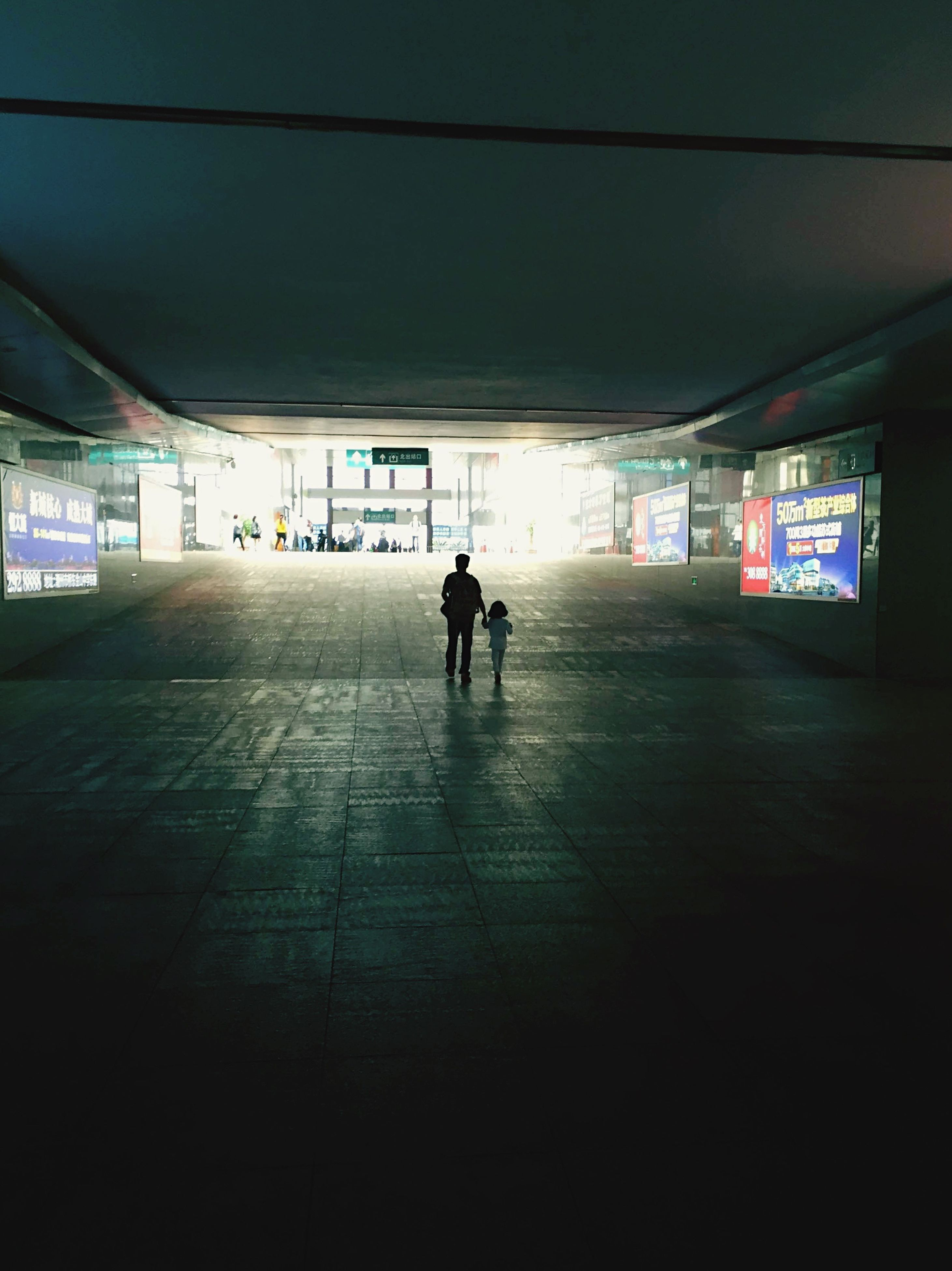 indoors, full length, men, illuminated, walking, lifestyles, ceiling, rear view, tunnel, person, the way forward, subway, transportation, leisure activity, architecture, built structure, silhouette, subway station