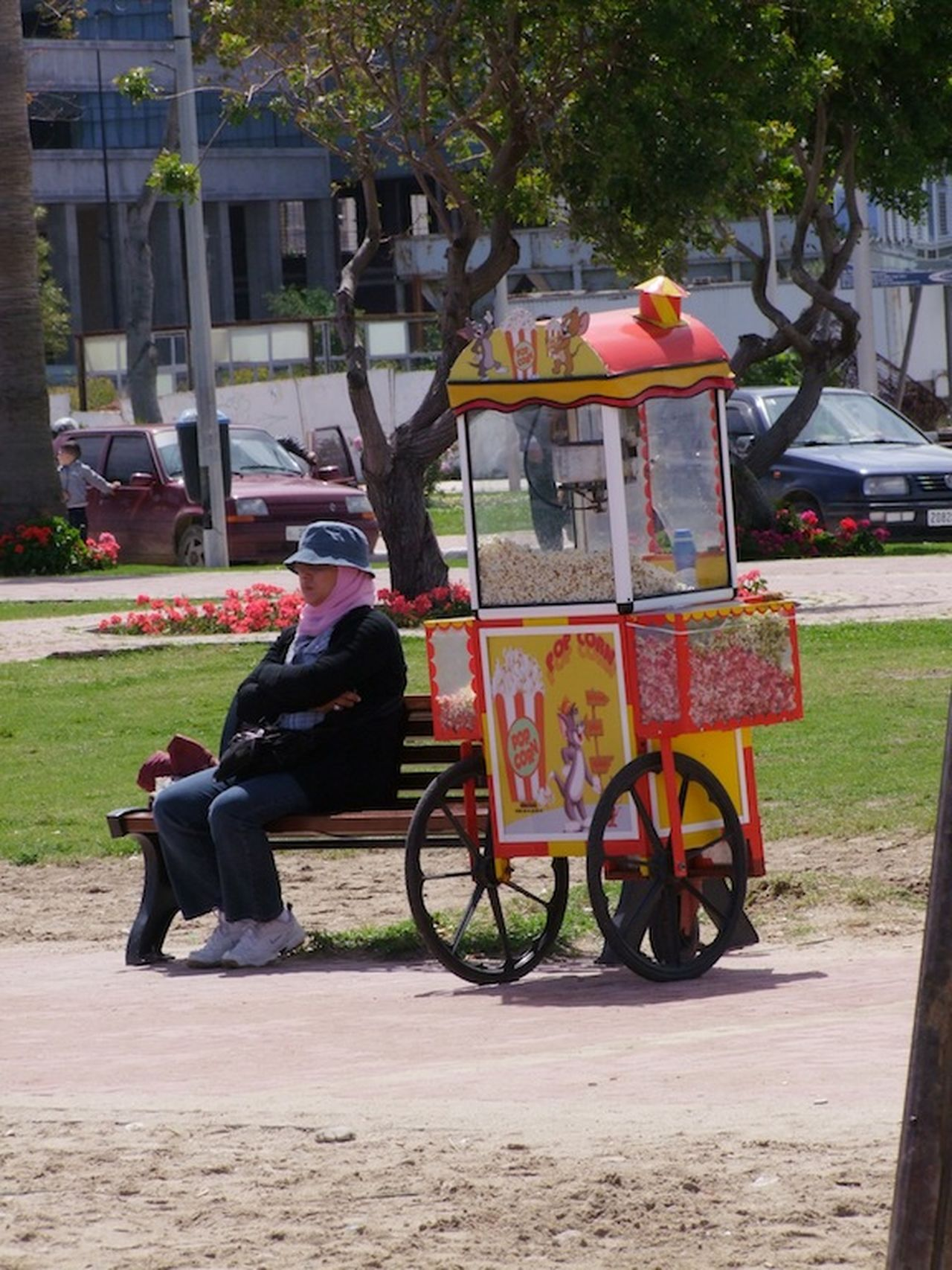 Popcorn Seller Beach Bench Cart Colourful Composition Culture Food Full Frame Lawn Making A Living Morocco Outdoor Photography Popcorn Popcorn Seller Sitting Snacks Tangier Tourism Tourist Attraction  Traditional Trees Woman