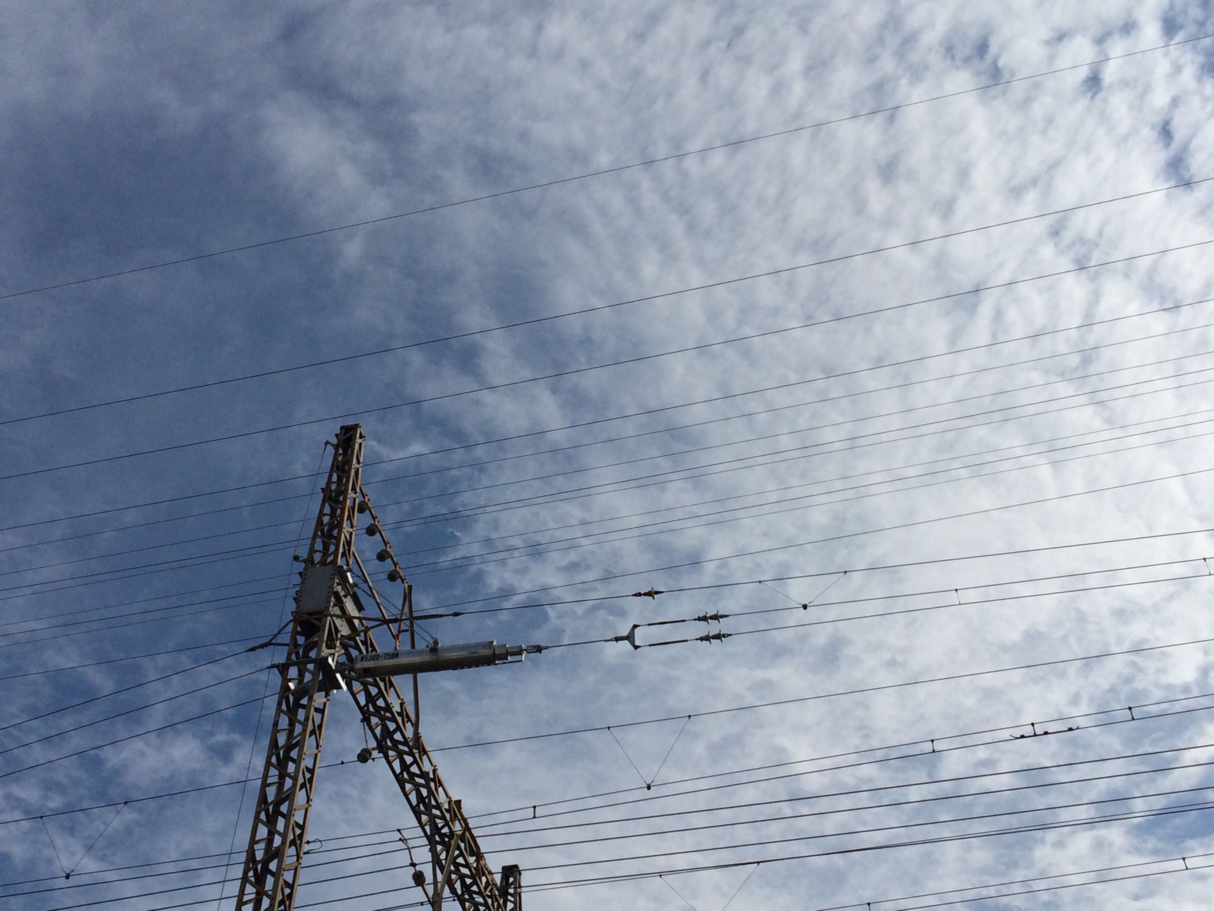 low angle view, sky, power line, electricity pylon, cloud - sky, connection, electricity, power supply, cable, technology, cloudy, fuel and power generation, cloud, built structure, day, outdoors, no people, weather, blue, nature
