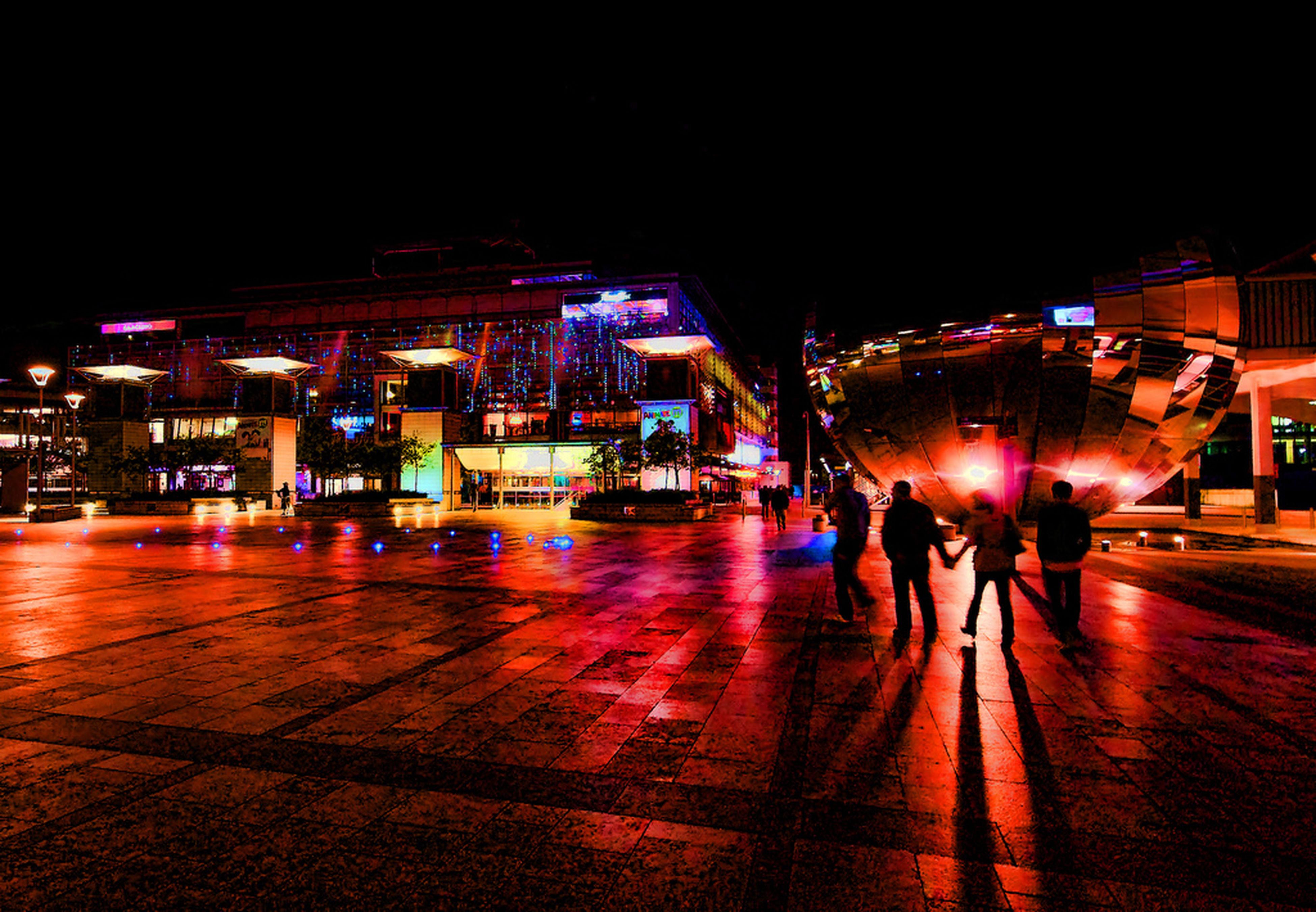 night, illuminated, building exterior, city, architecture, built structure, city life, street, walking, lifestyles, men, person, leisure activity, full length, blurred motion, motion, sidewalk, lighting equipment, city street