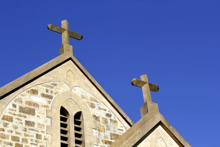 Stone crucifixes tower above a church in South Australia Architecture Australia Blue Building Exterior Built Structure Christian Christianity Church Architecture Cross Crucifix Day Faith Forgiveness No People Outdoors Place Of Worship Religion Religious Architecture Sky Spirituality Stone Crucifix