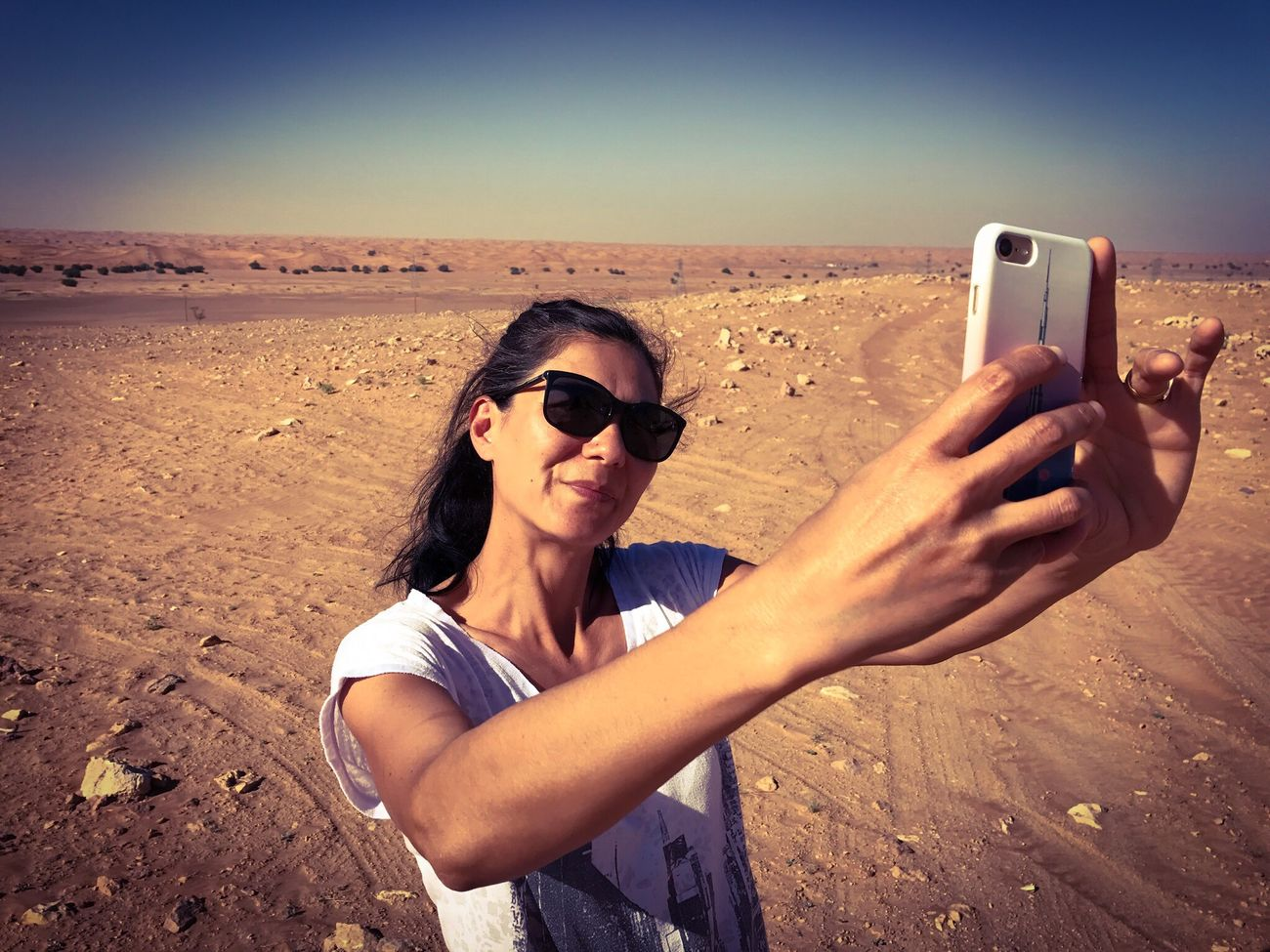 Woman taking a selfie in the desert Photography Themes Photo Messaging Smart Phone Portable Information Device Selfie Wireless Technology Photographing Sunglasses Technology Communication Mobile Phone Holding One Person Desert Safari IPhone Sand Outdoors Young Adult Real People Day People