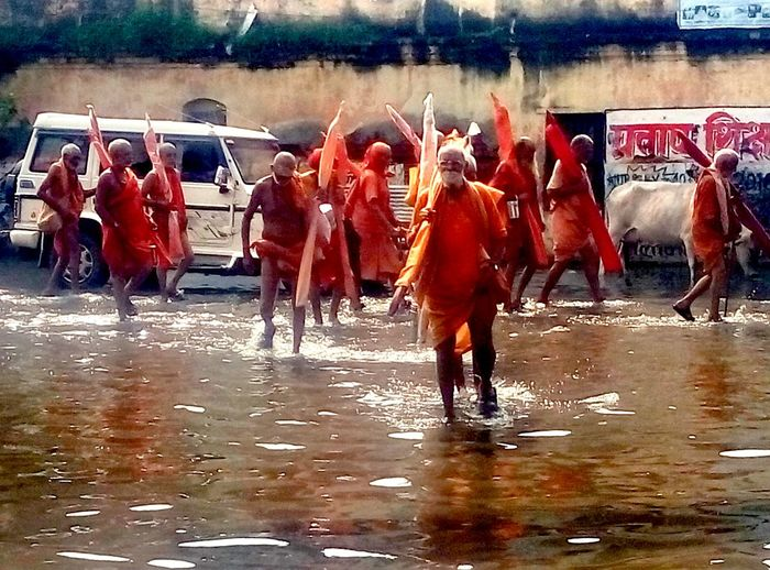Pilgrims walking in the water during August flood in Varanasi Water Men Gangs Flood Holy Men Sadhu Shiva Month Of Shiva Indian Baba Walking On The Water Real Magic Orange Clothes Flood In India Varanasi Assi Ghat Pilgrims Pilgrimage Magic Of India The Moments Of Magic