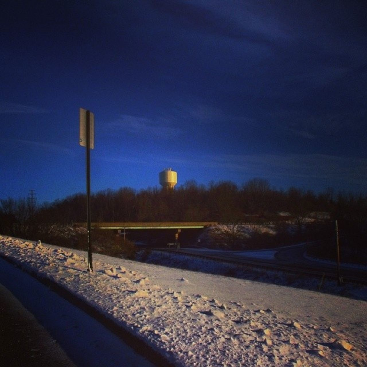 road, cold temperature, blue, snow, transportation, no people, sky, winter, nature, outdoors, tree, water tower - storage tank, day