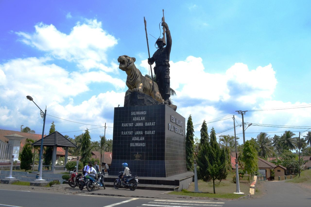 Statue Of Soldier And Tiger On Pedestal And People On Bike