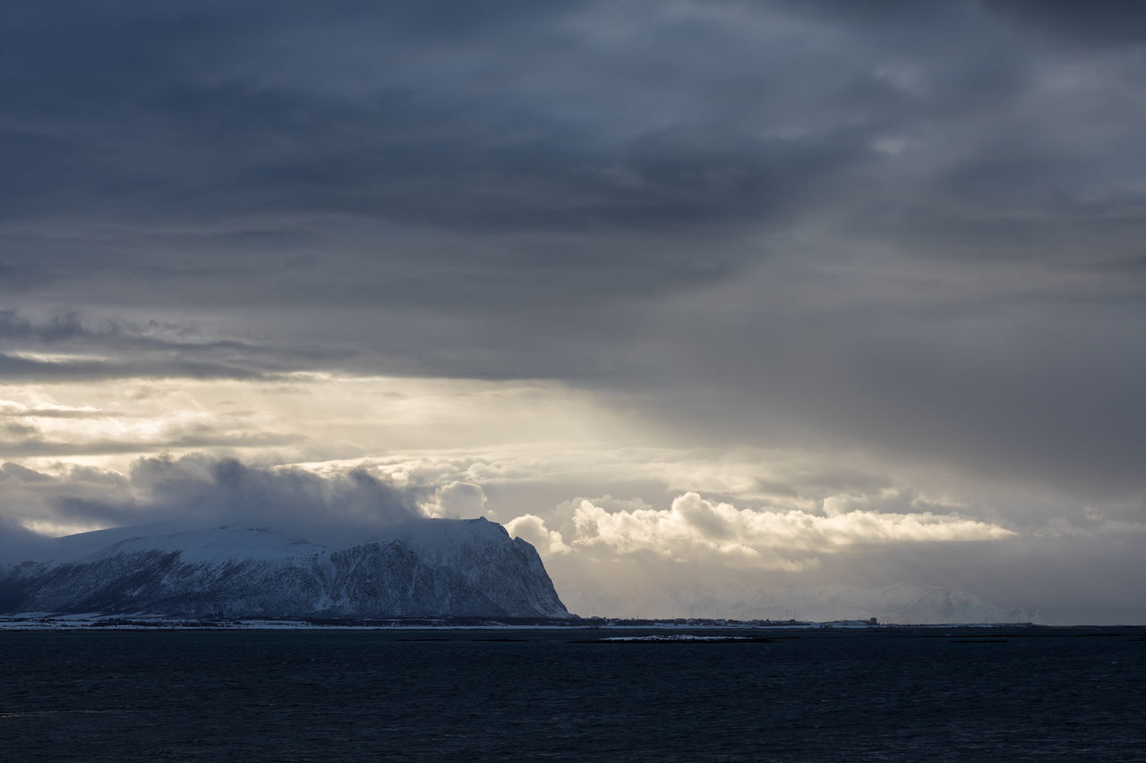 Dark clouds over snowcapped mountain in sea with some sunbeams shining through Beauty In Nature Cloud - Sky Cloudscape Cold Temperature Dramatic Sky Extreme Weather Gray Landscape Lofoten And Vesteral Islands Moody Sky Mountain Nature No People Norwegian Sea Outdoors Sea Snow Snowcapped Mountain Sunbeam Sunlight Sunset Water Waterfront Weather Winter The Great Outdoors - 2017 EyeEm Awards
