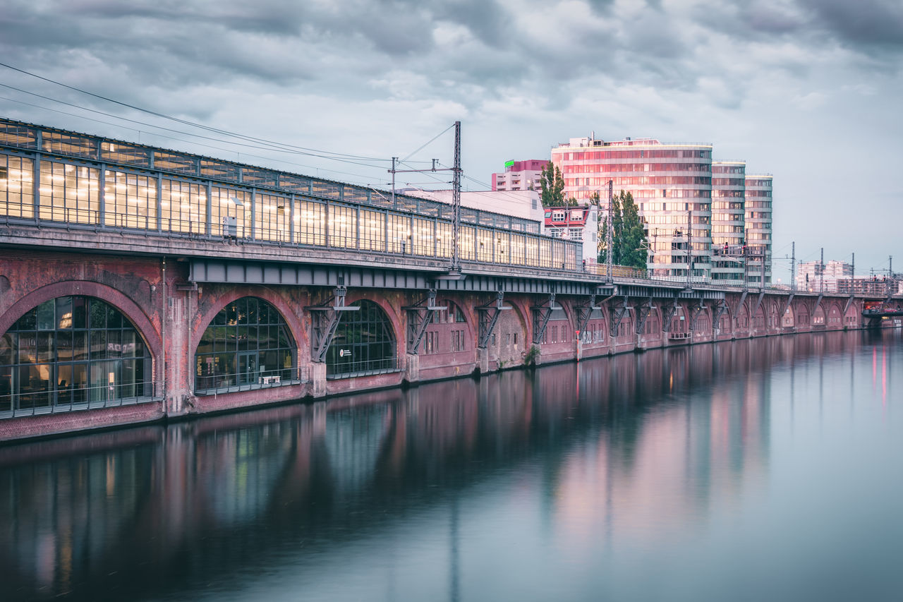 architecture, built structure, connection, bridge - man made structure, transportation, sky, waterfront, cloud - sky, reflection, water, no people, river, outdoors, building exterior, day