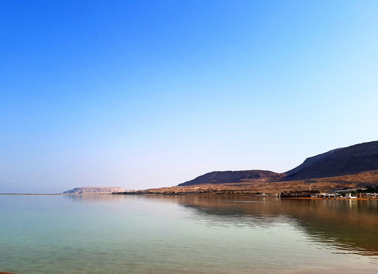 water, copy space, clear sky, tranquil scene, tranquility, beauty in nature, nature, mountain, scenics, blue, outdoors, no people, reflection, sea, day, sky